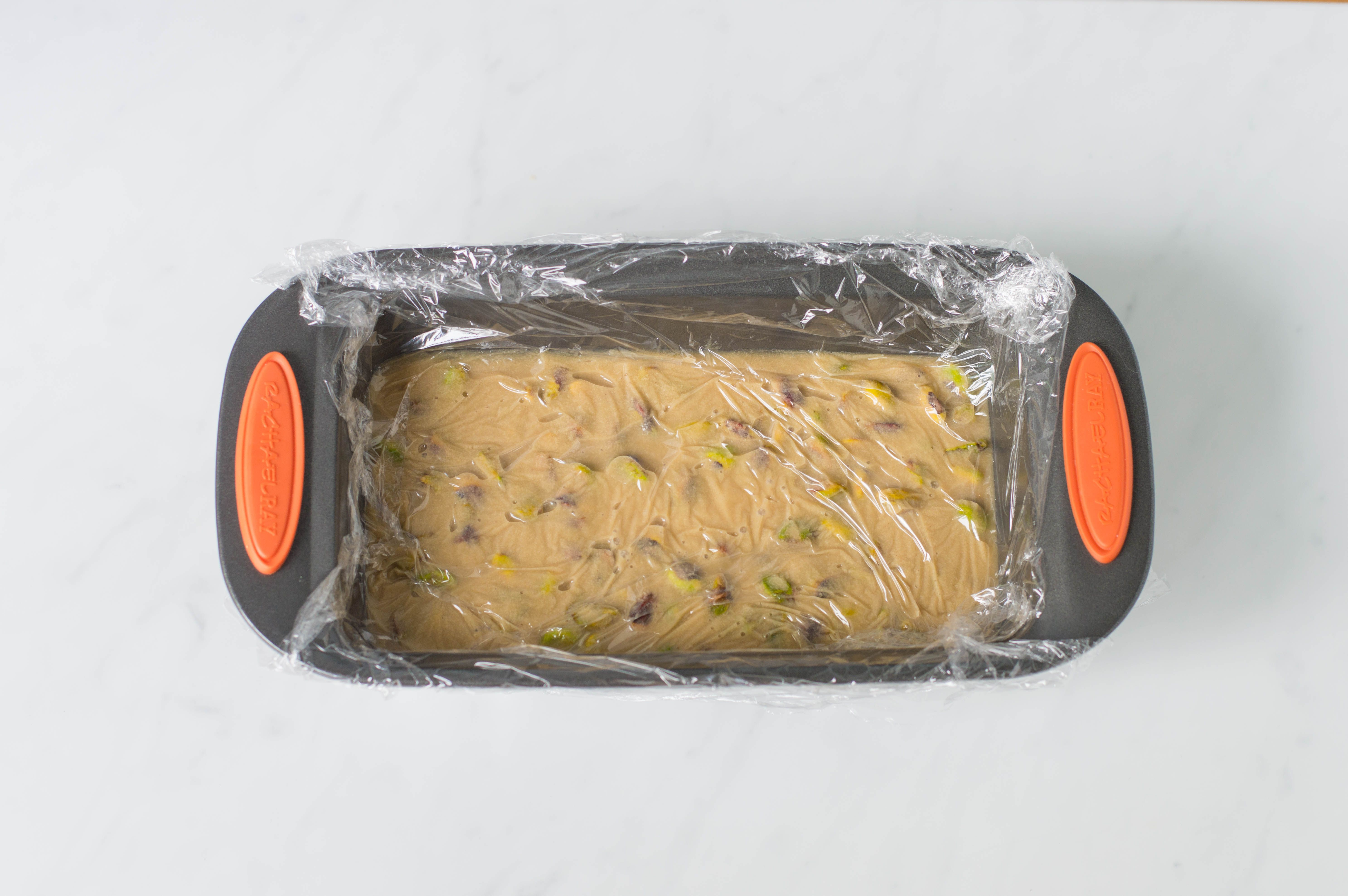 Halvah in a loaf pan covered with plastic wrap