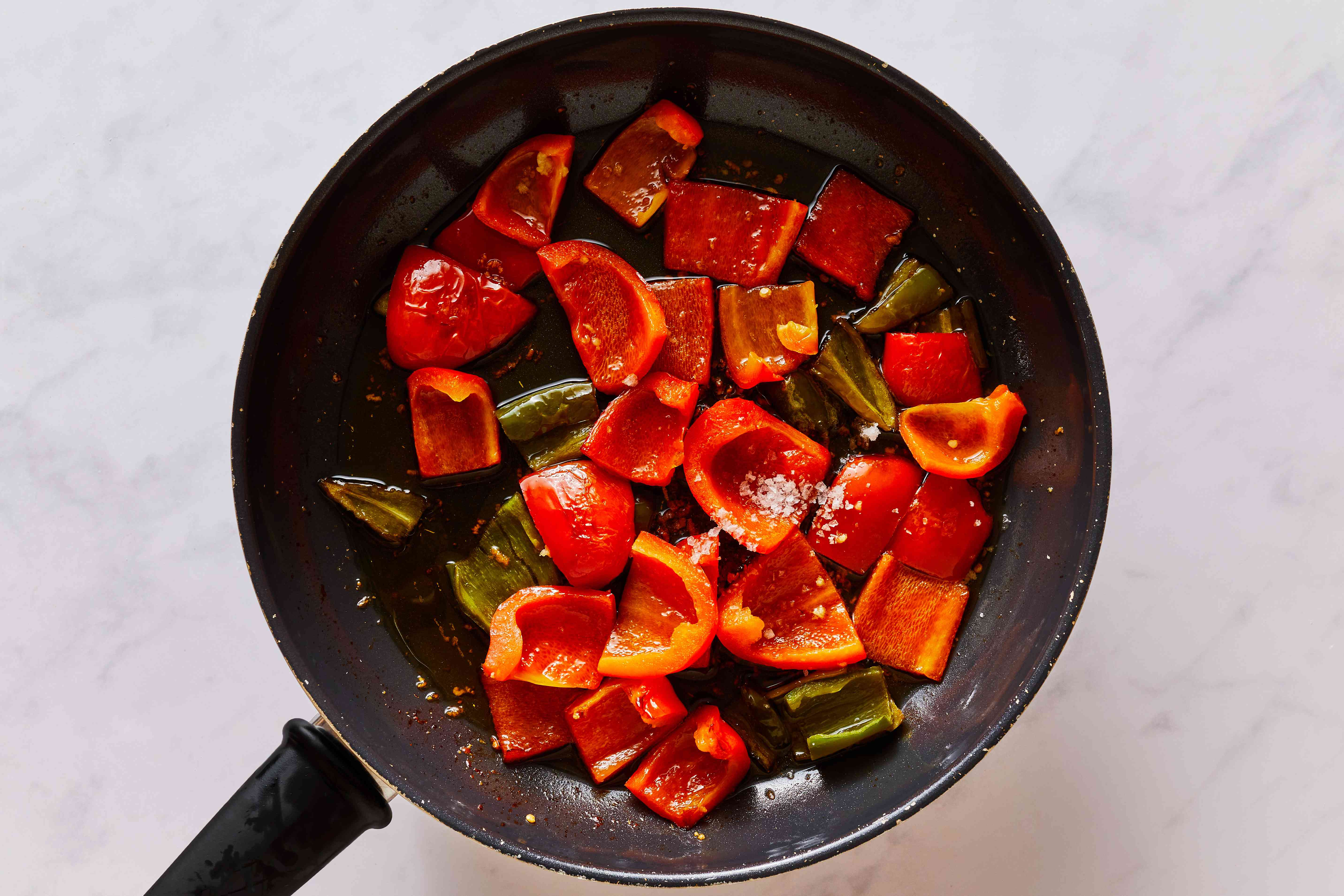 When the olive oil is hot, add the peppers and garlic into the frying pan