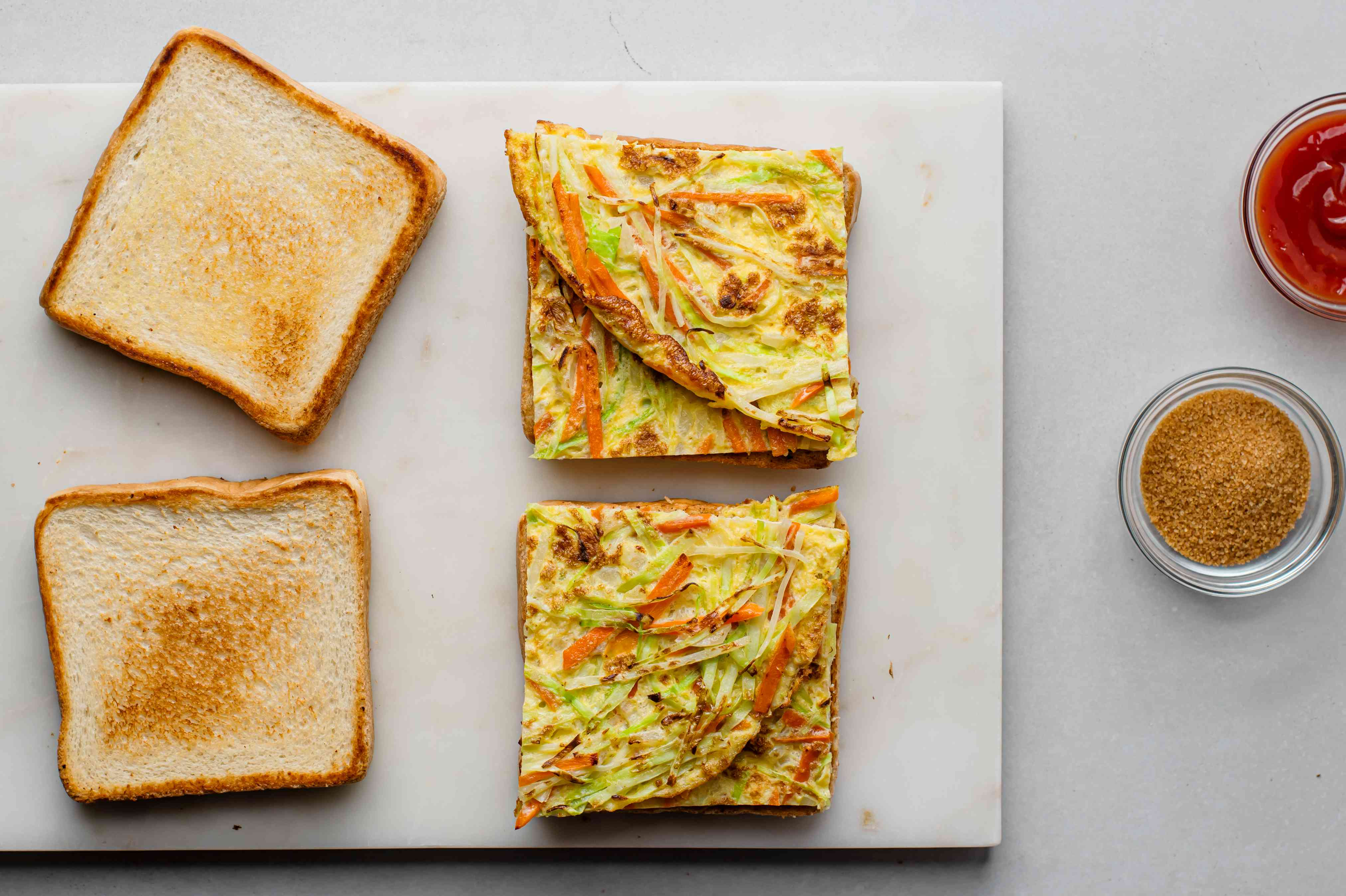 fried eggs with vegetables on white bread
