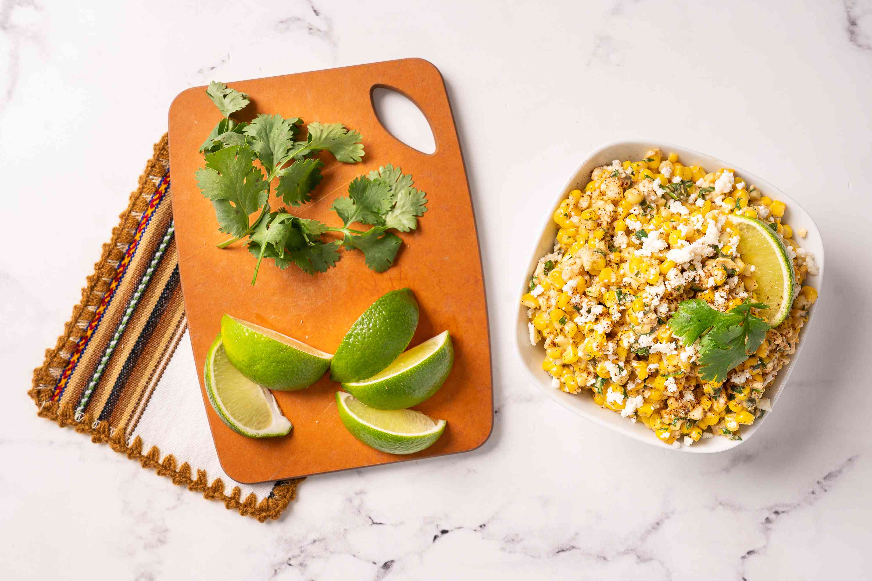 Esquites with limes and cilantro on the side