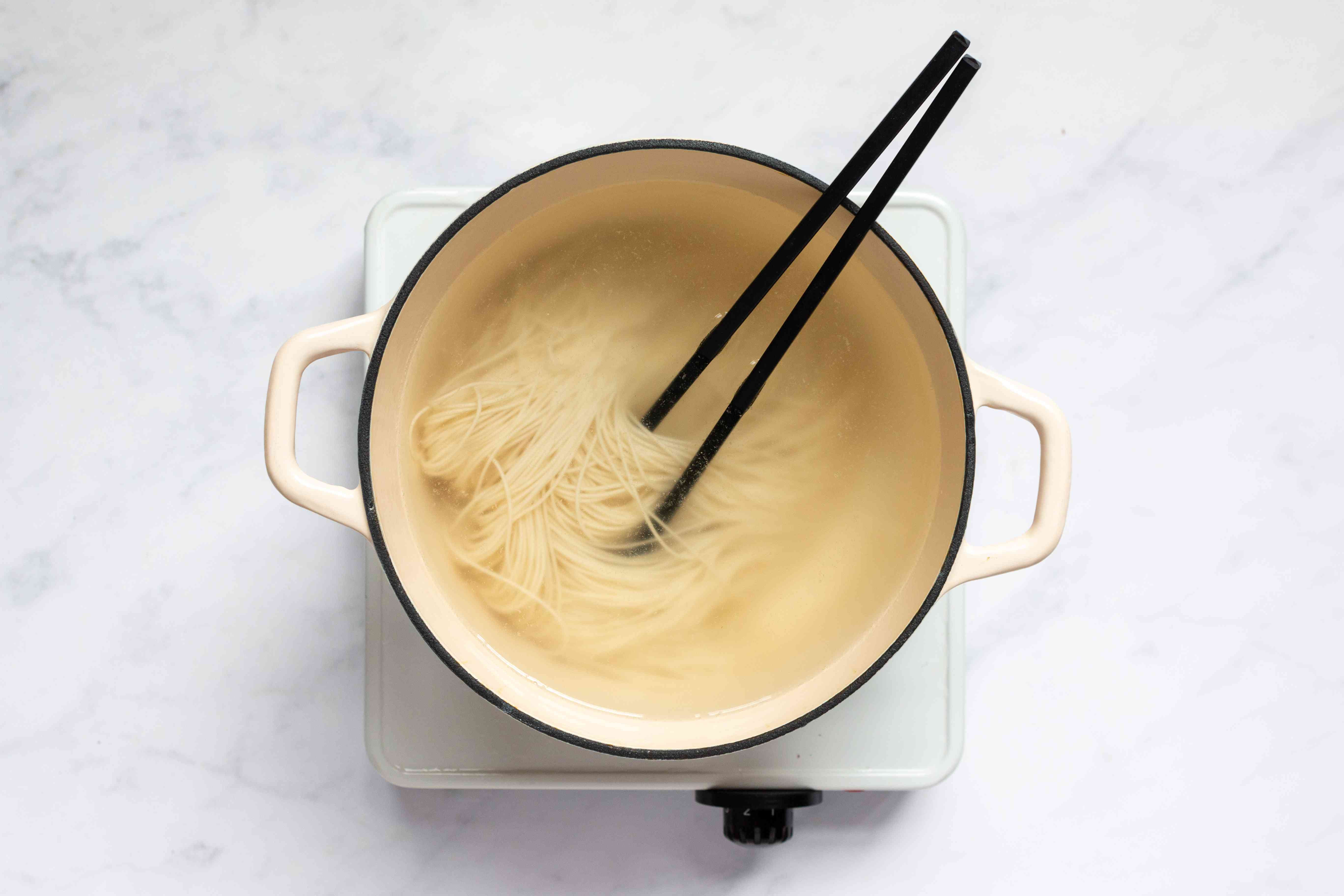 noodles in a pot with water, chopsticks