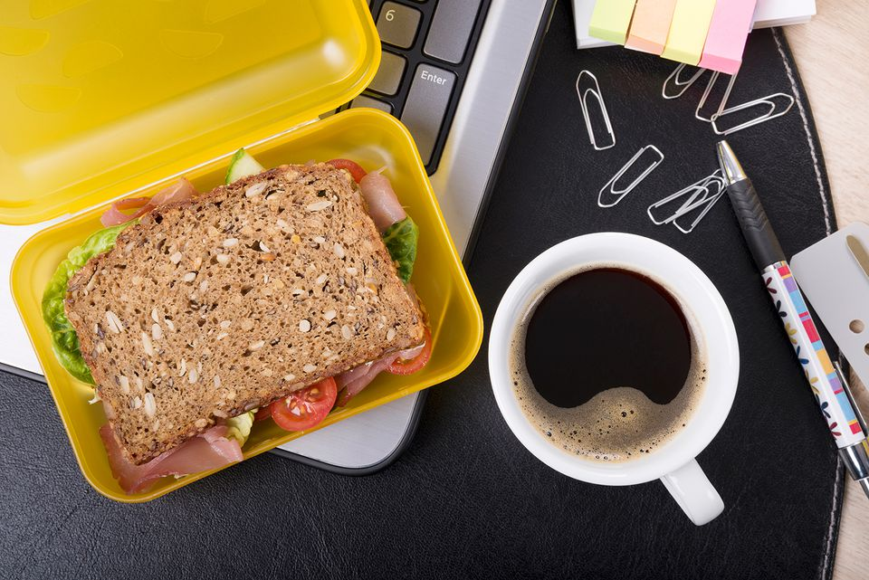 Workplace with lunchbox and cup of coffee