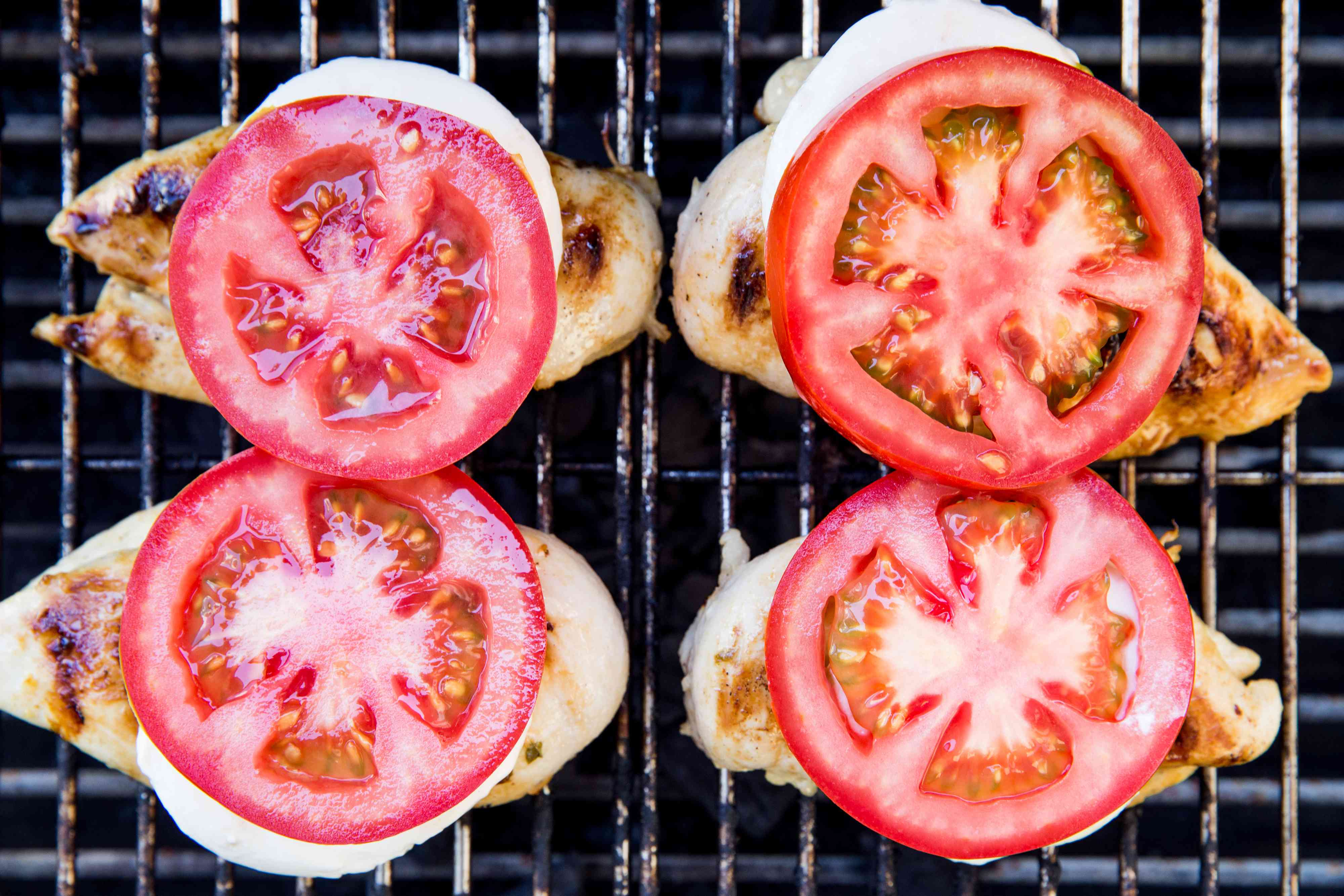 chicken with mozzarella and tomato on top, on the grill