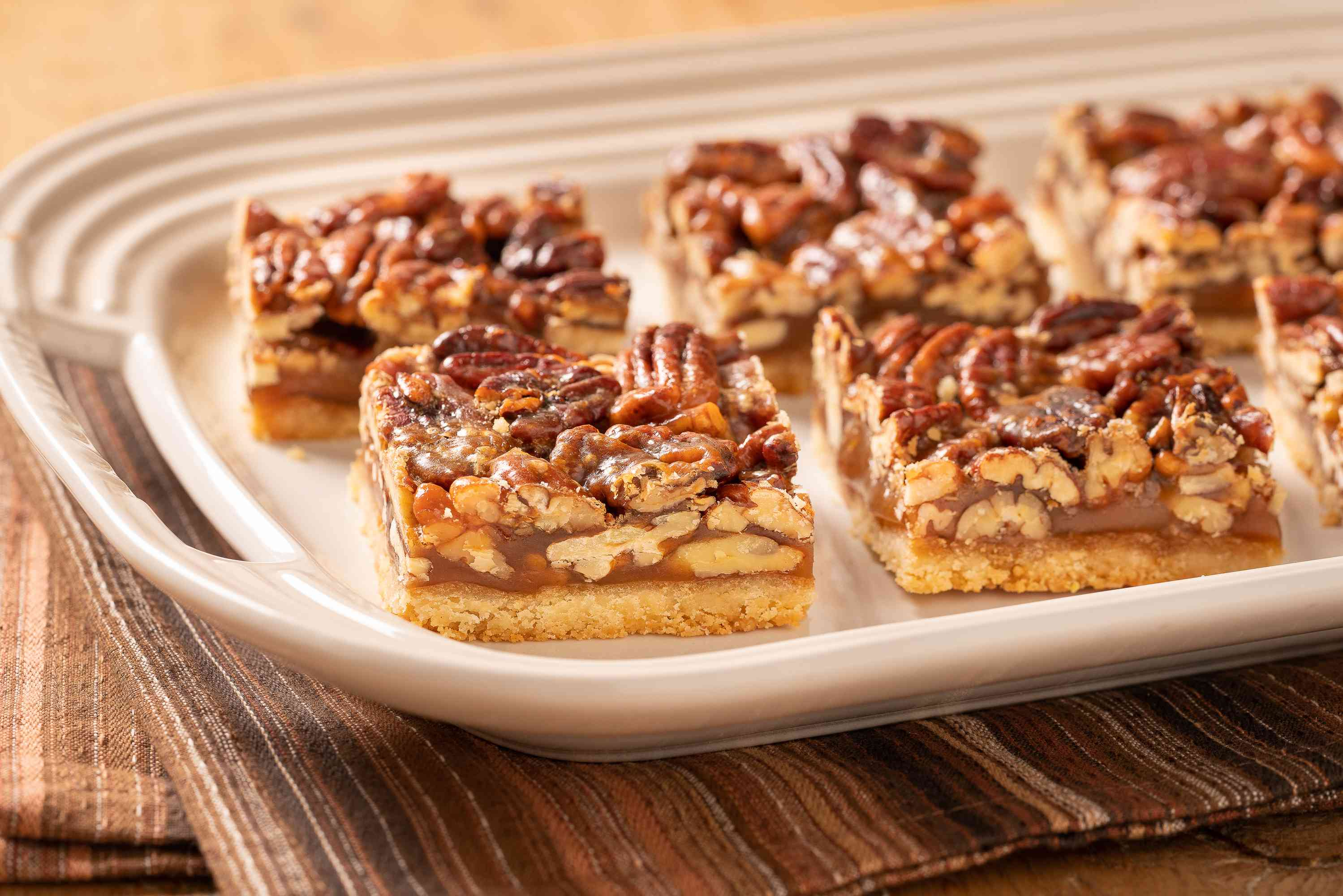 Pecan pie bars on a white serving plate