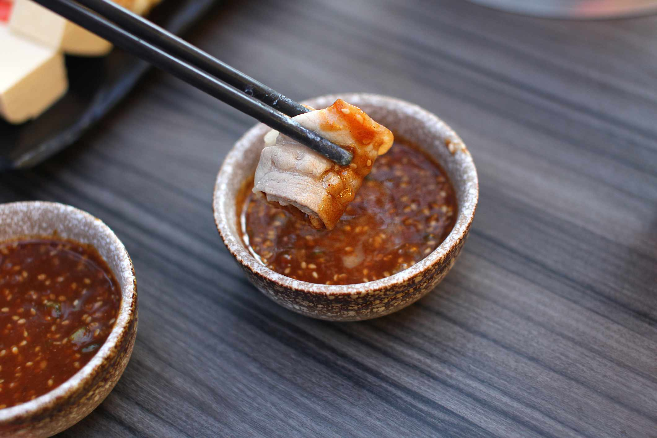 Dipping meat in Hoisin sauce