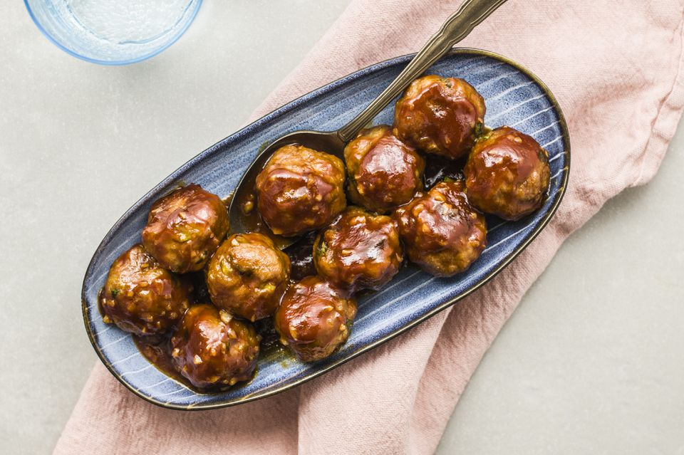 Honey garlic pork meatballs in a bowl with a serving spoon