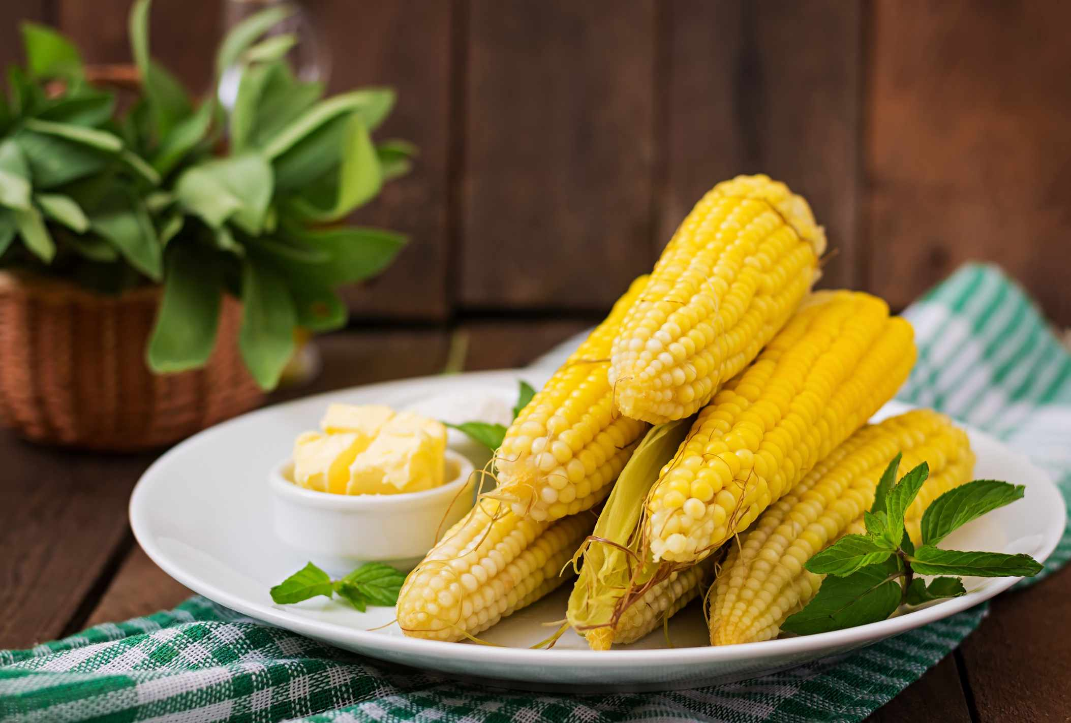 A plate of corn on the cob with a side a butter