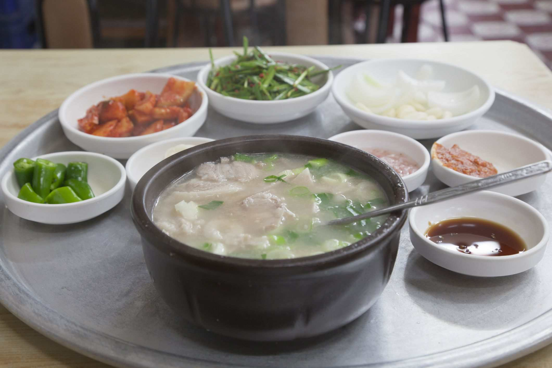 Sam Gae Tang (Korean chicken soup) in large bowl other toppings nearby