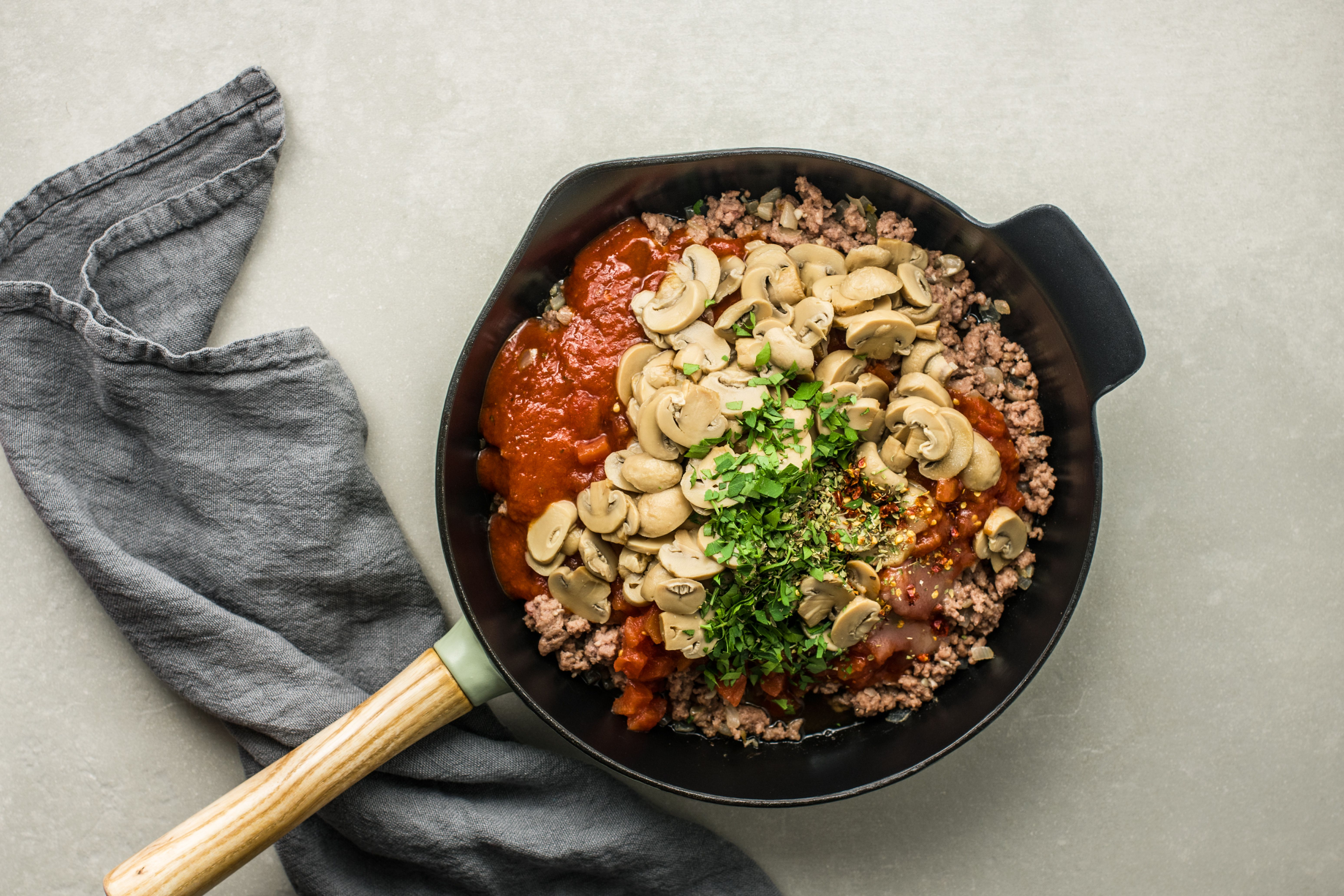 tomatoes, tomato sauce, parsley, and sugar and mushrooms added to skillet