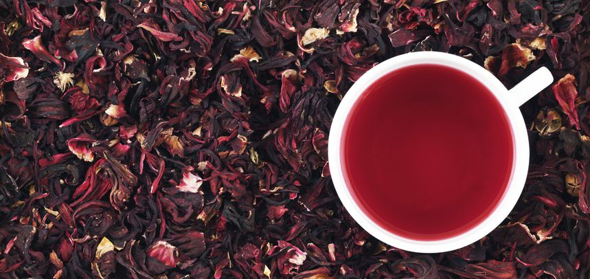 Dried hibiscus petals and cup of hibiscus tea