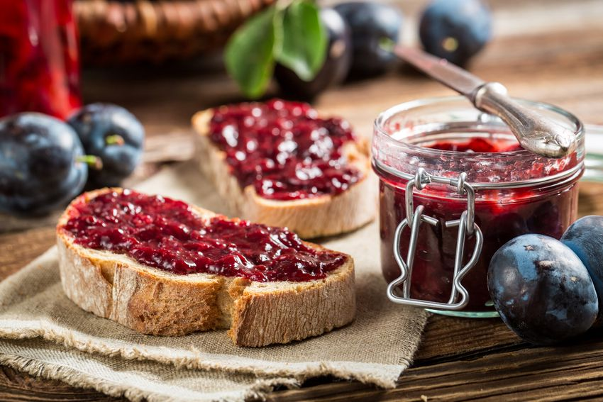 a glass jar of red-colored jam next to pieces of bread and blueberries