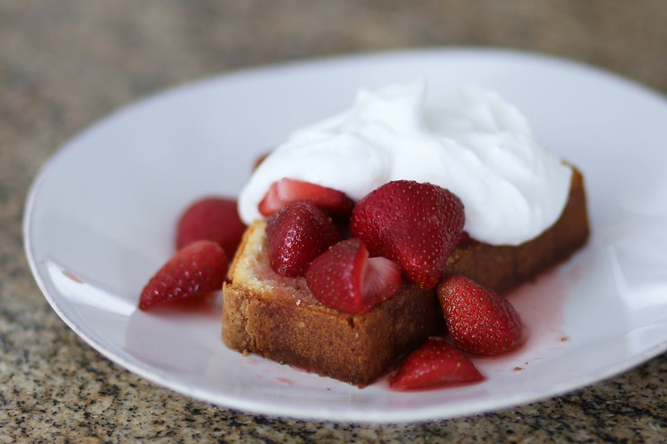 Cold oven pound cake served with whipped cream and strawberries