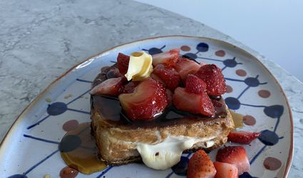 Stuffed French Toast with strawberries and maple syrup on plate.