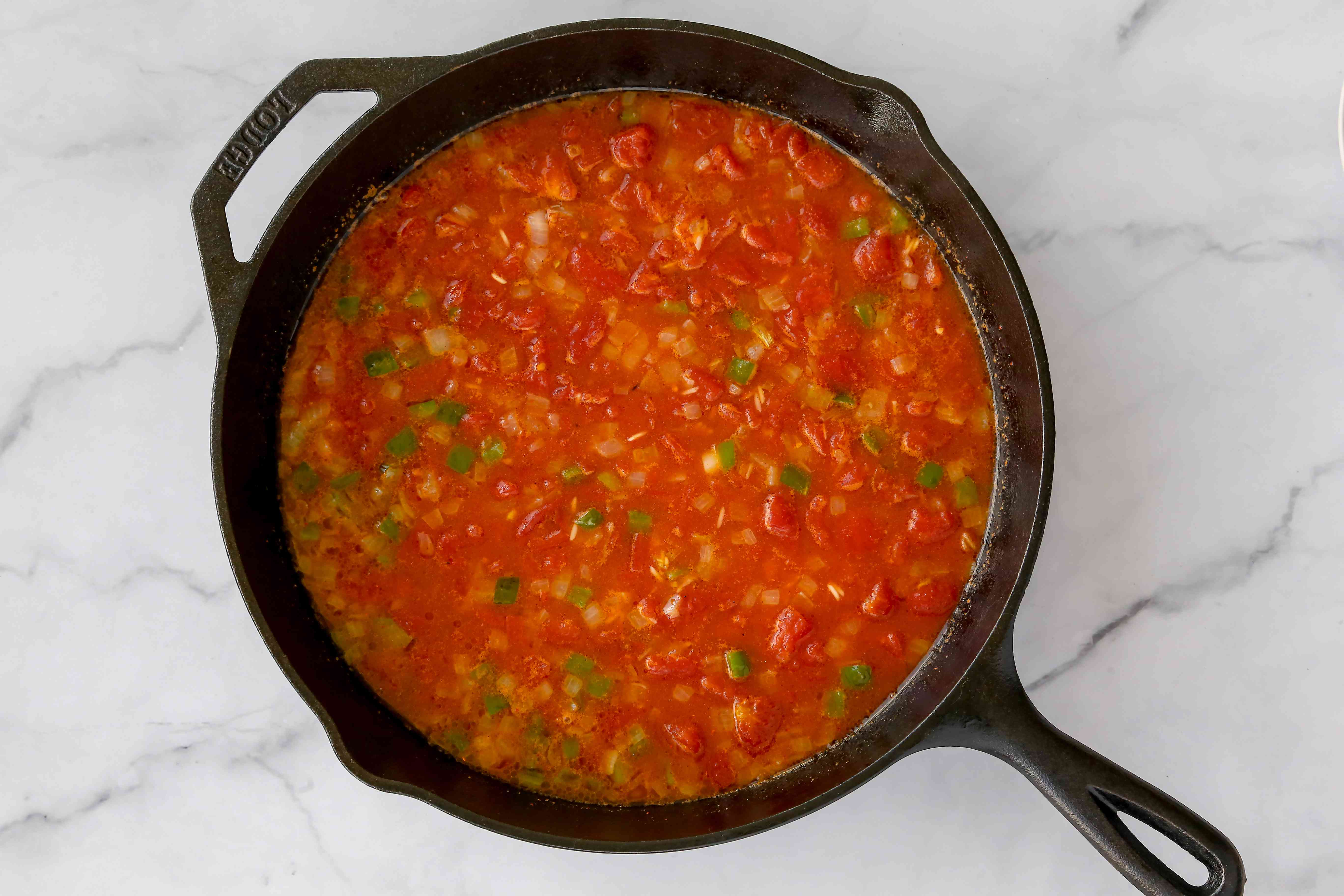Add tomatoes, chili powder, cumin, salt, and beef broth to the rice mixture in the skillet