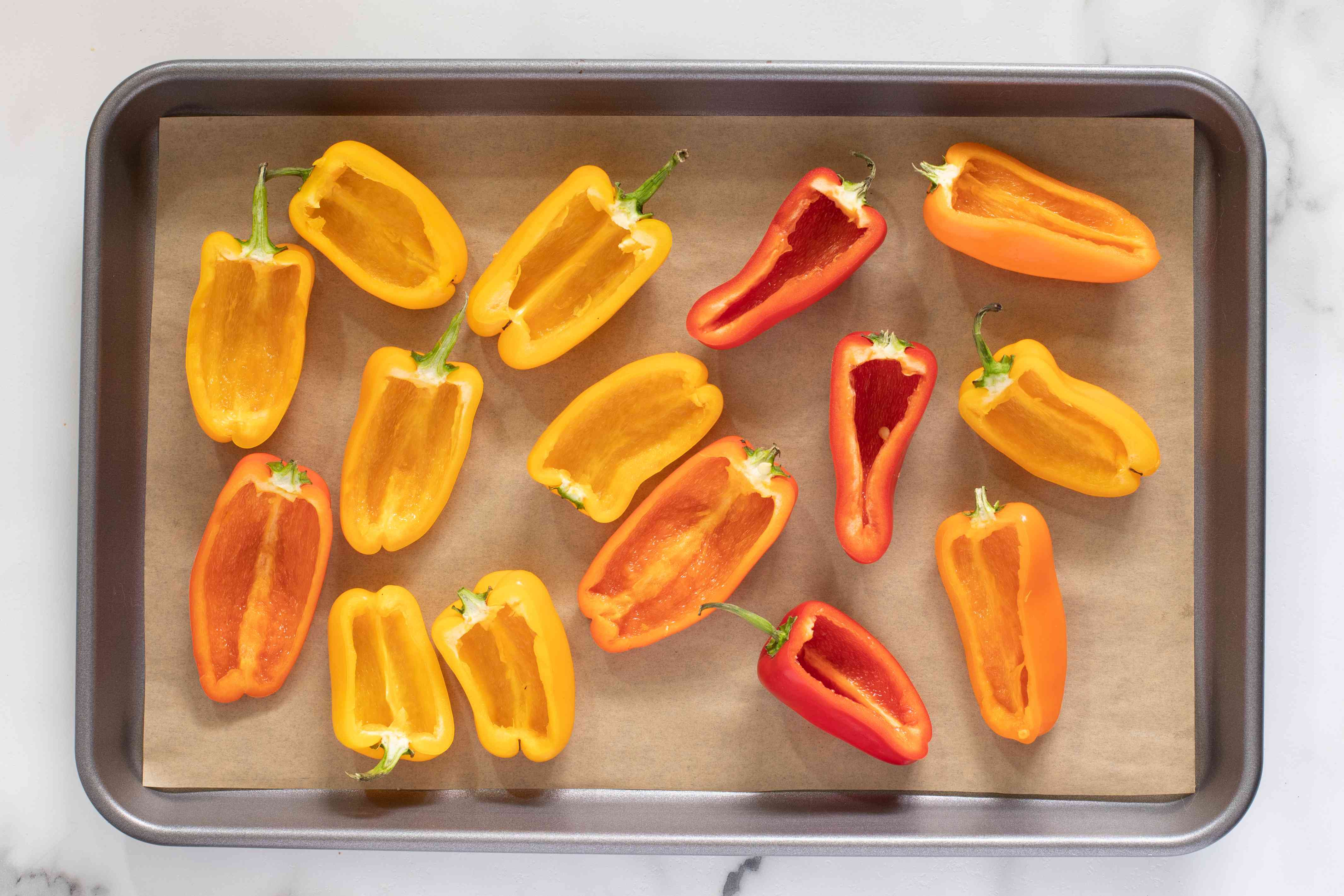 mini peppers halved on the baking sheet