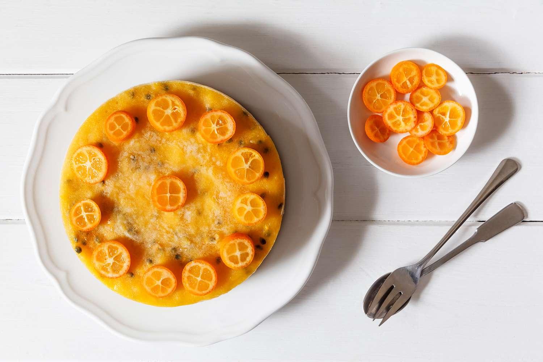 Mango passion fruit cake decorated with slices of kumquat