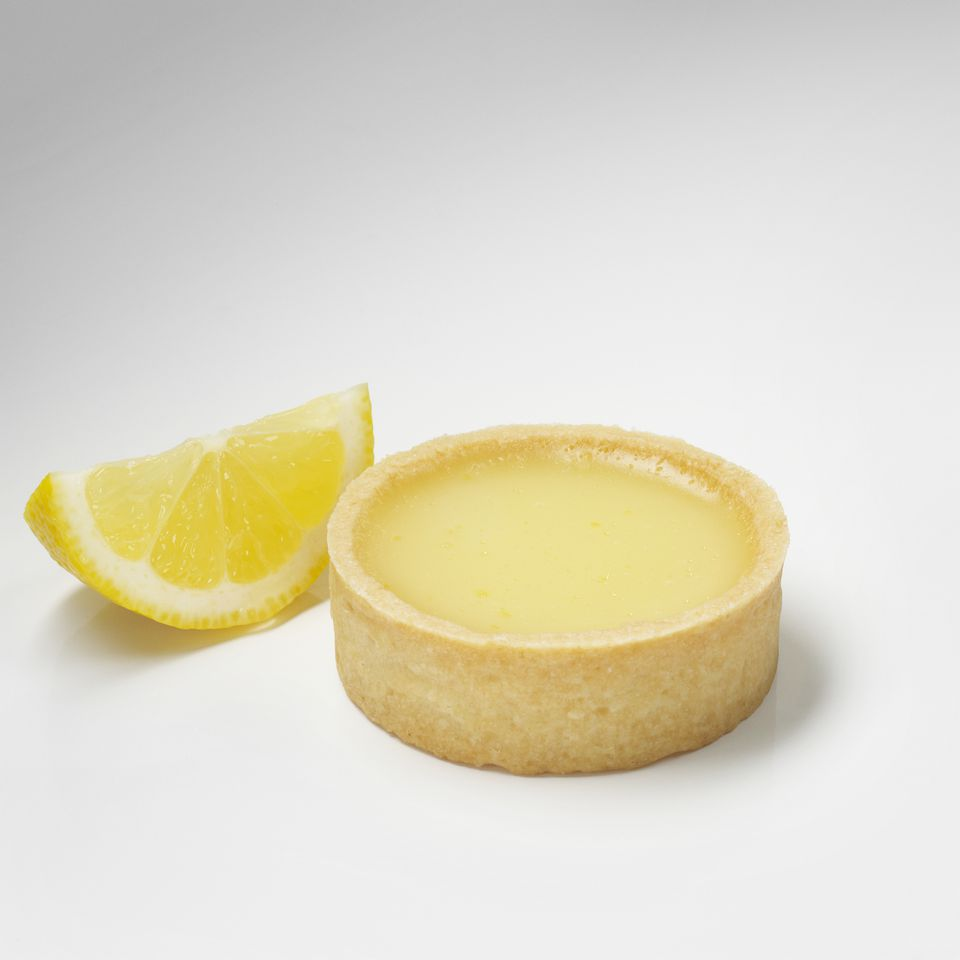 Lemon custard and a lemon wedge on a white background