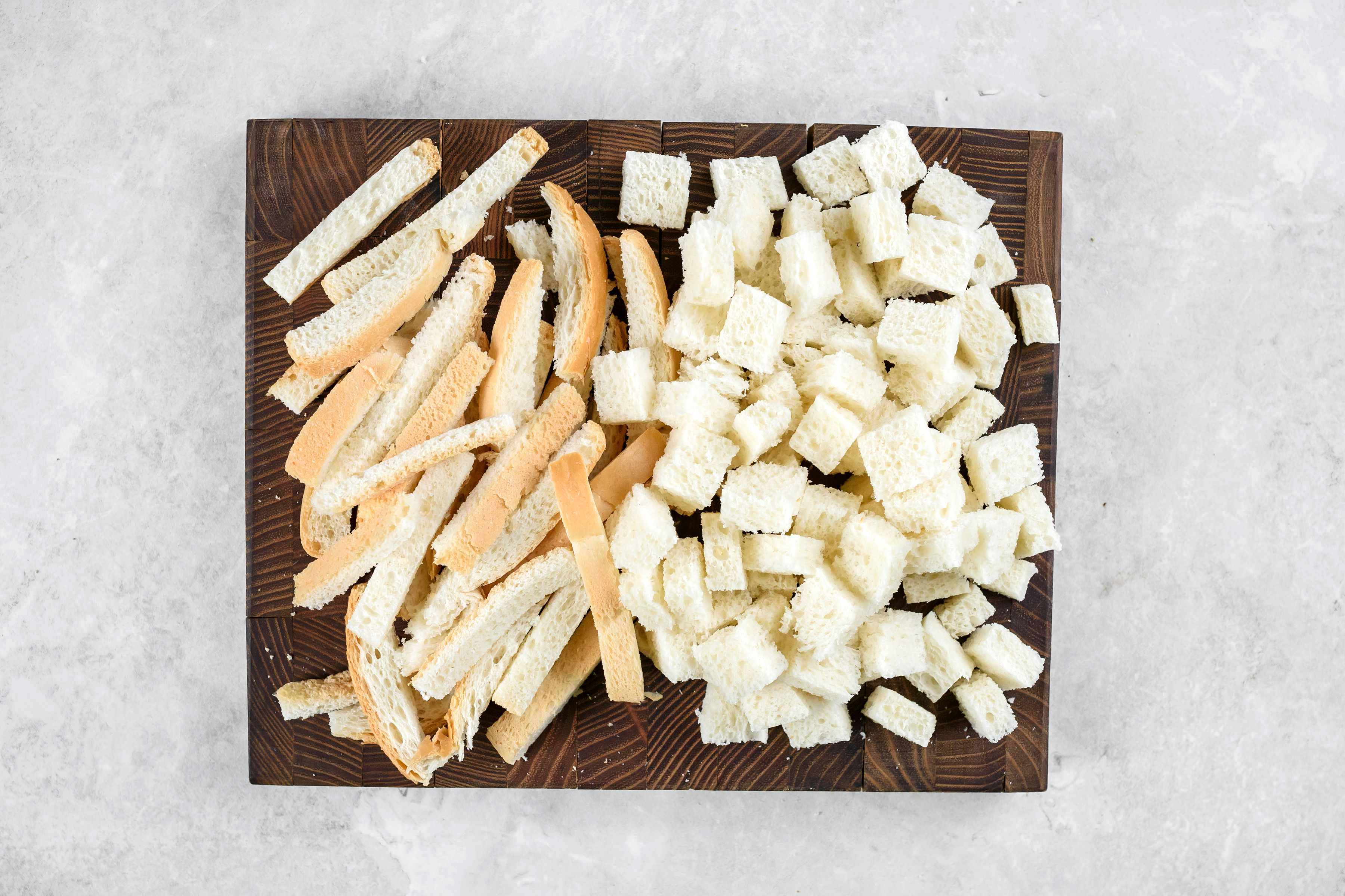 White bread on wooden cutting board, cut into cubes