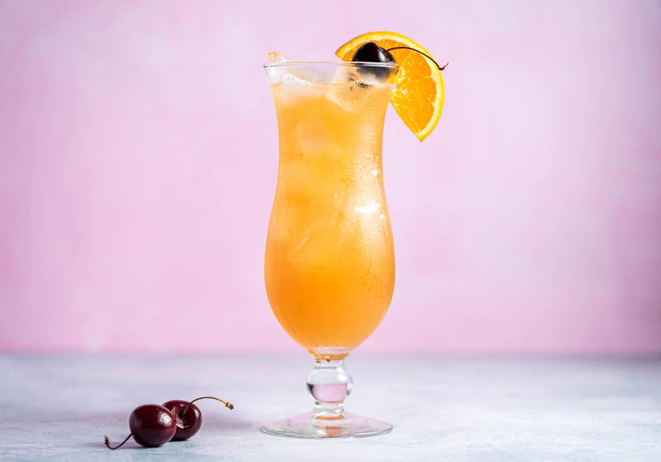 Classic hurricane cocktail with a cherry and orange slice garnish