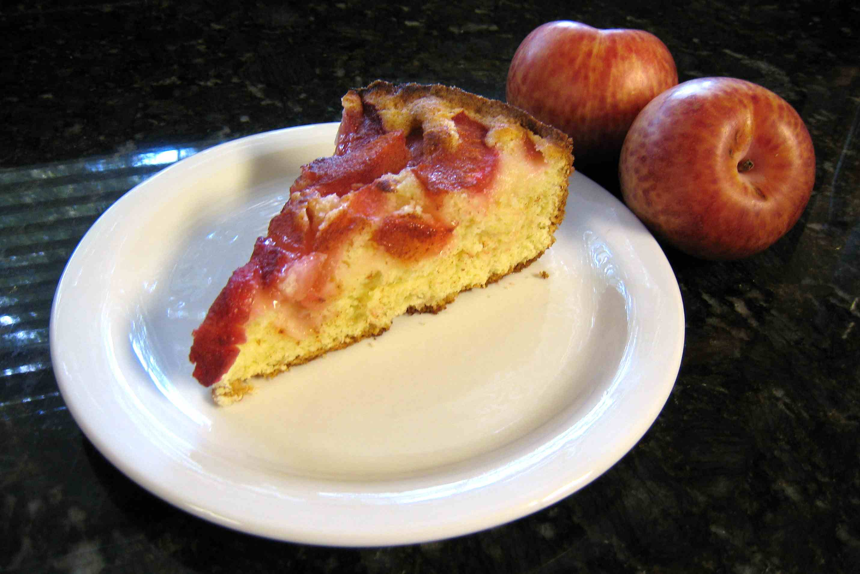 A slice of plum cake with fresh fruit