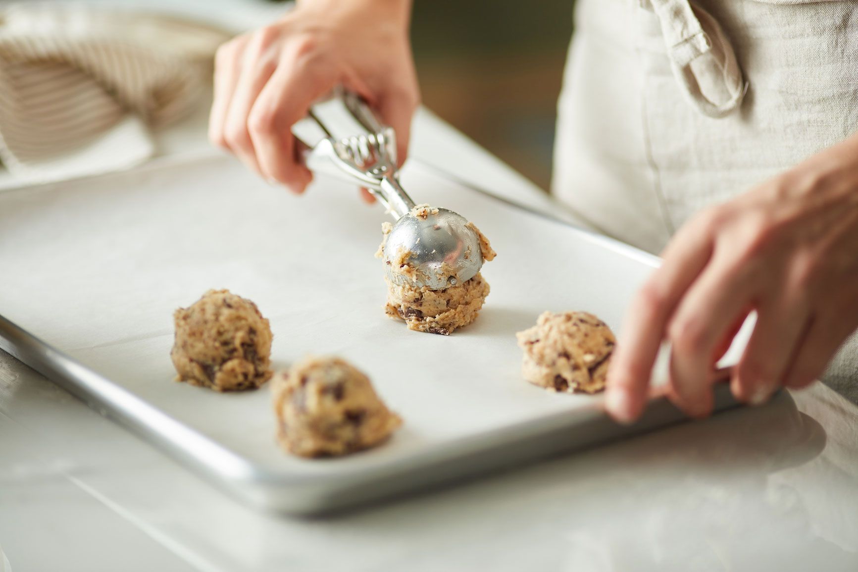 Scooping cookie dough onto a sheet pan