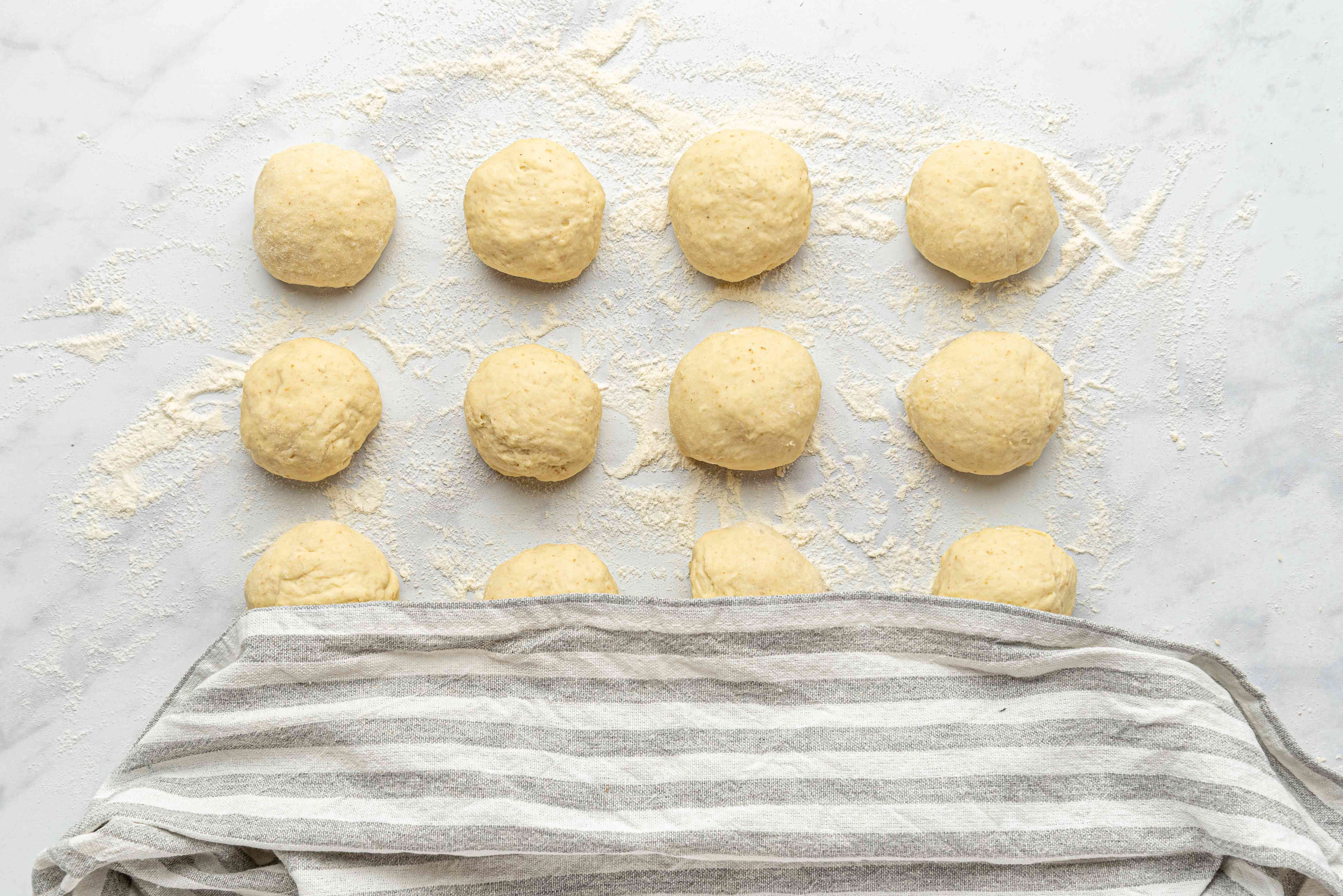 dough balls covered with a towel on a floured surface