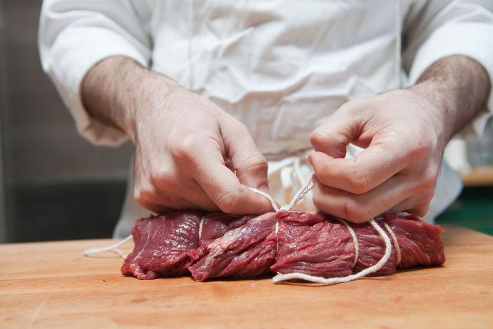 Butcher tying beef tenderloin