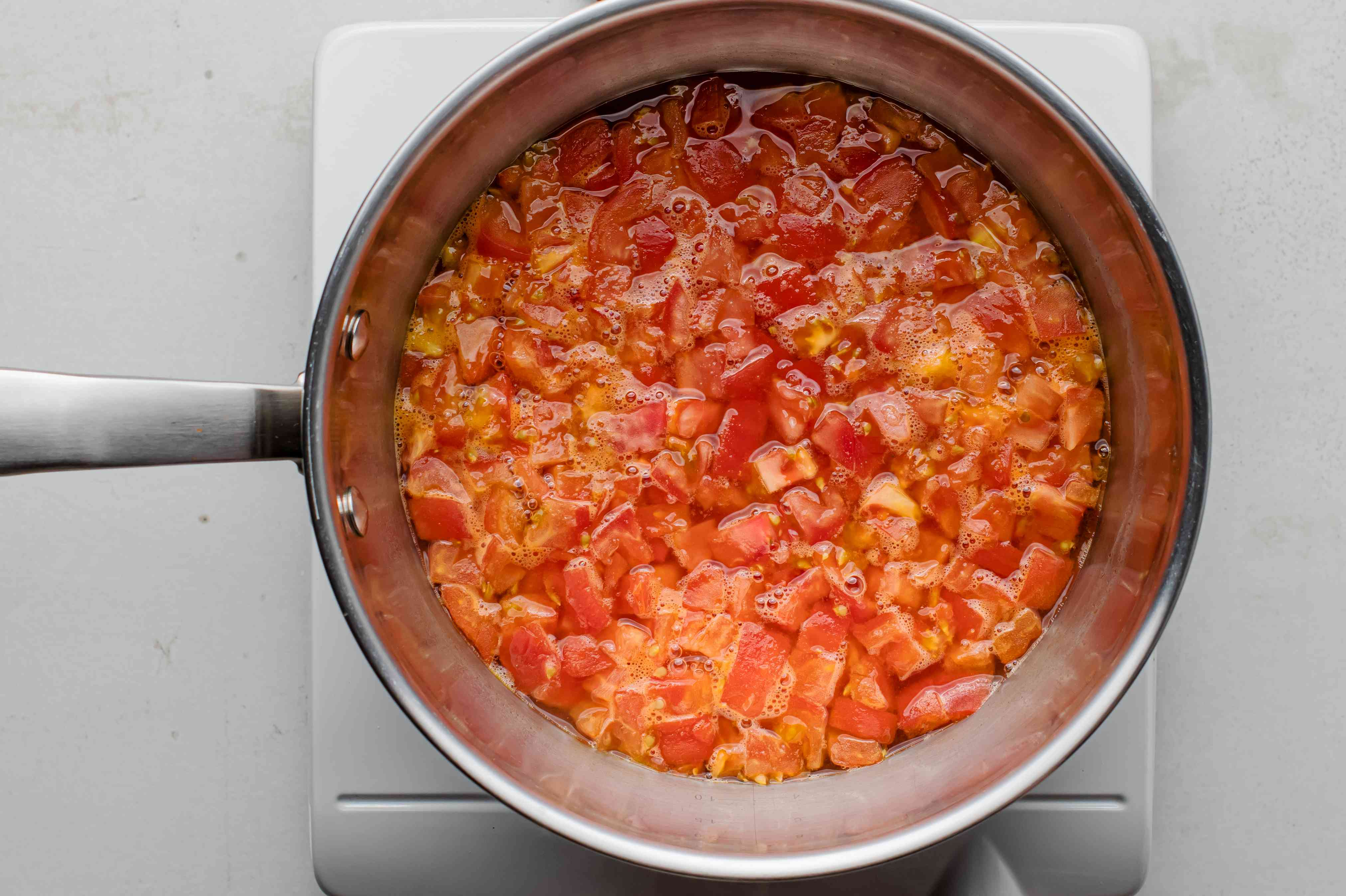 Tomatoes and chicken stock in a sauce pan on a burner