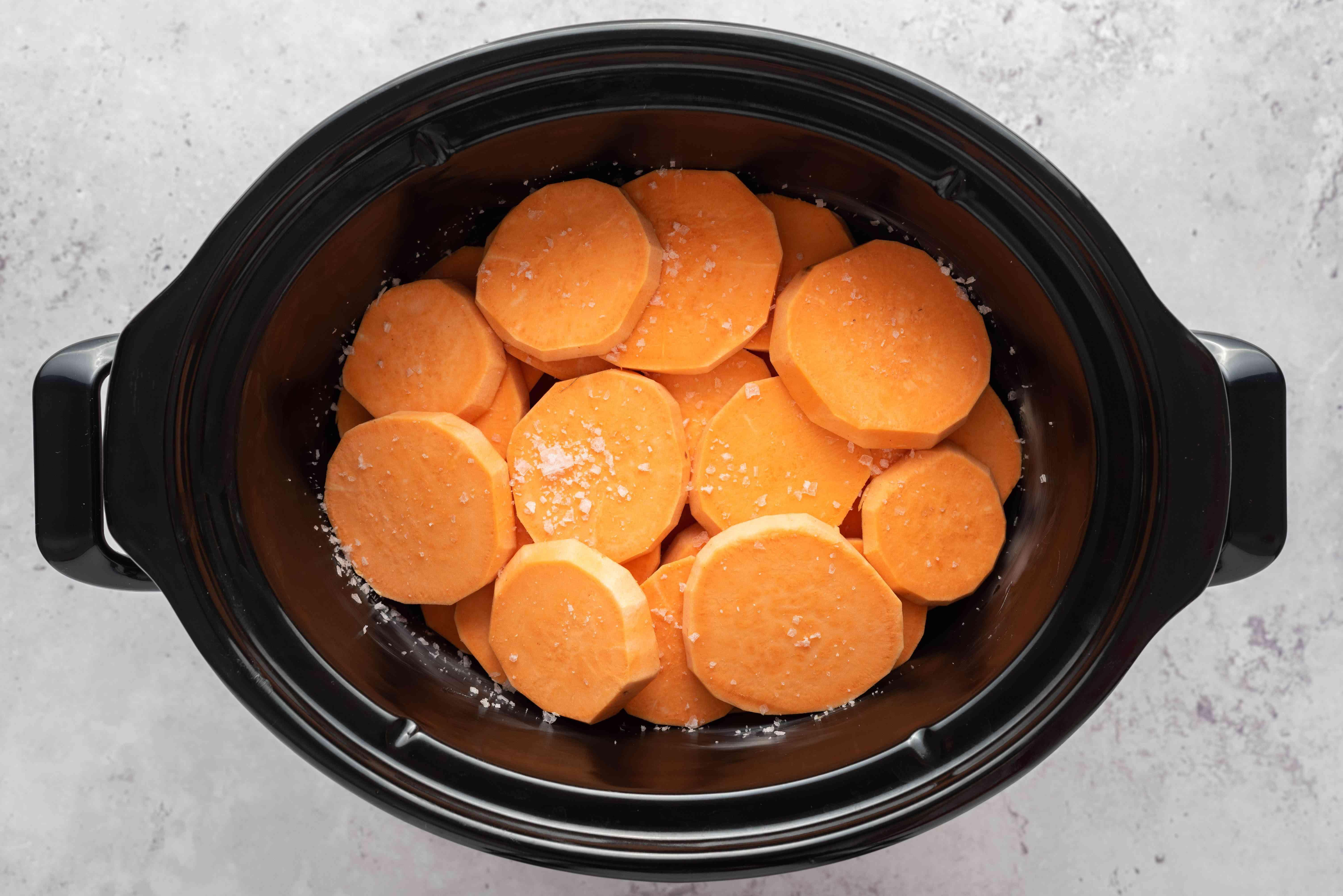 sliced sweet potatoes sprinkled with salt in a crockpot