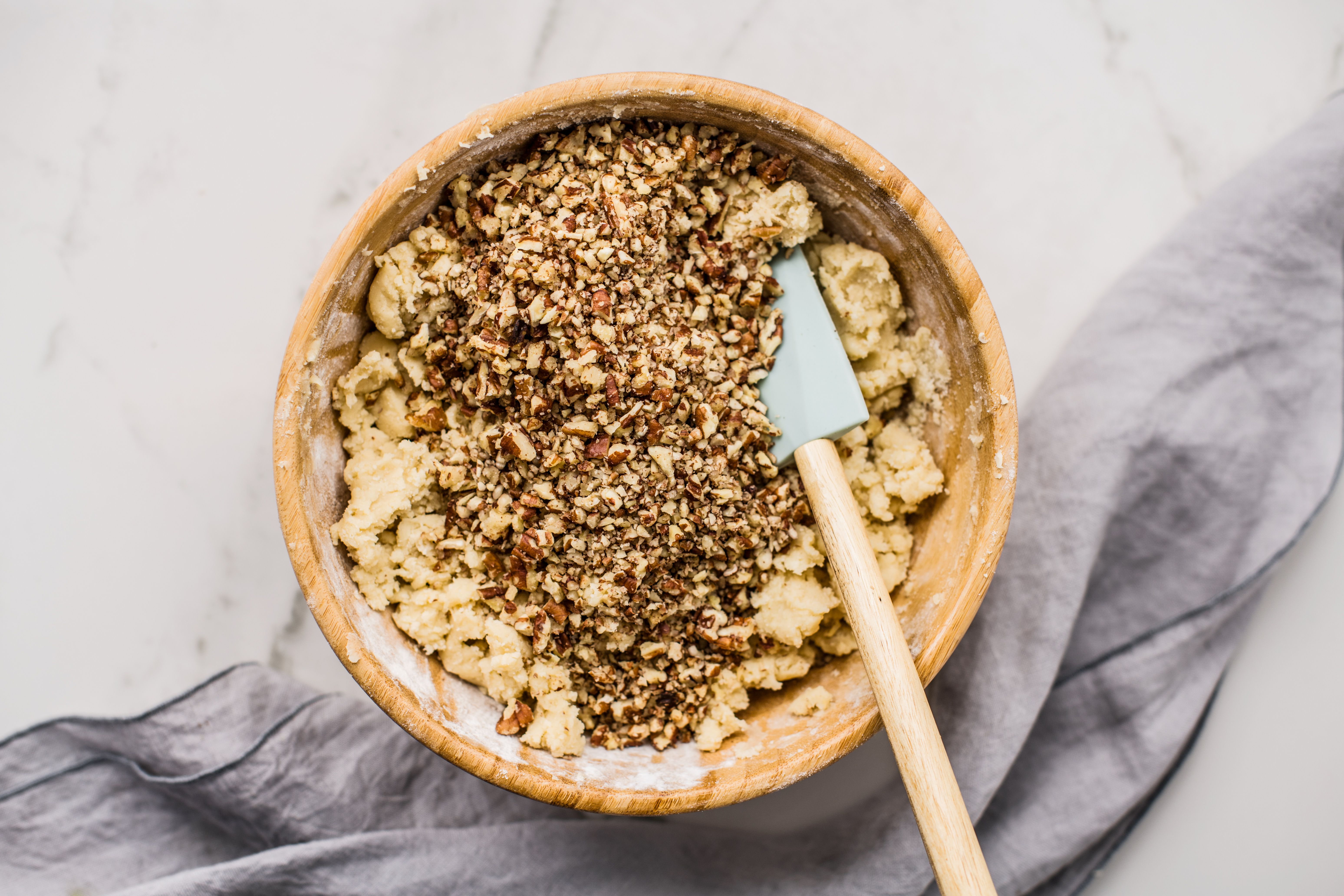 chopped pecans added to dough in bowl