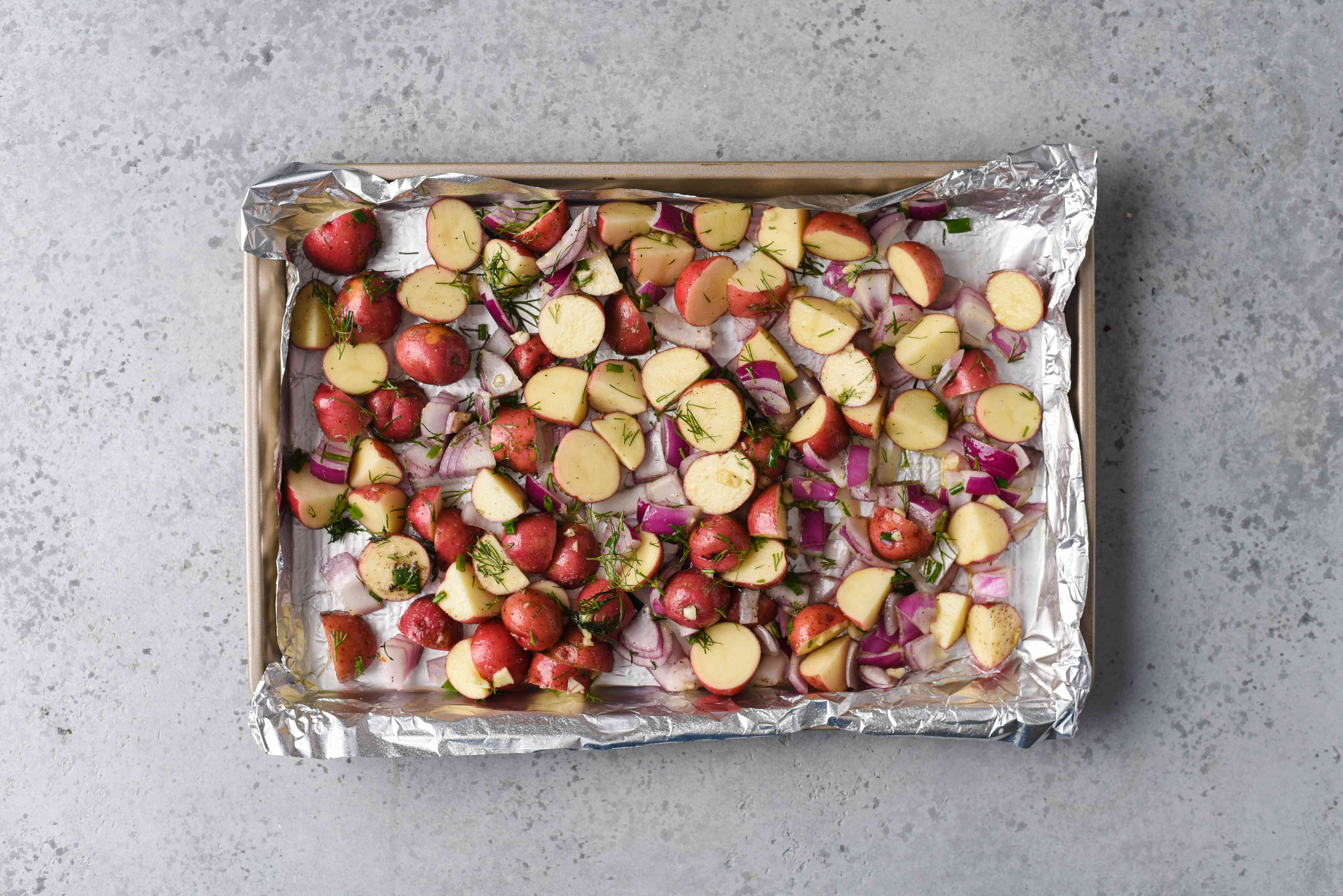 potatoes, onions and herbs on a baking sheet