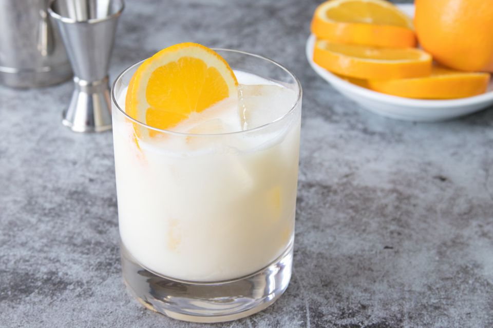 Orange creamsicle cocktail in a glass with orange slice garnish