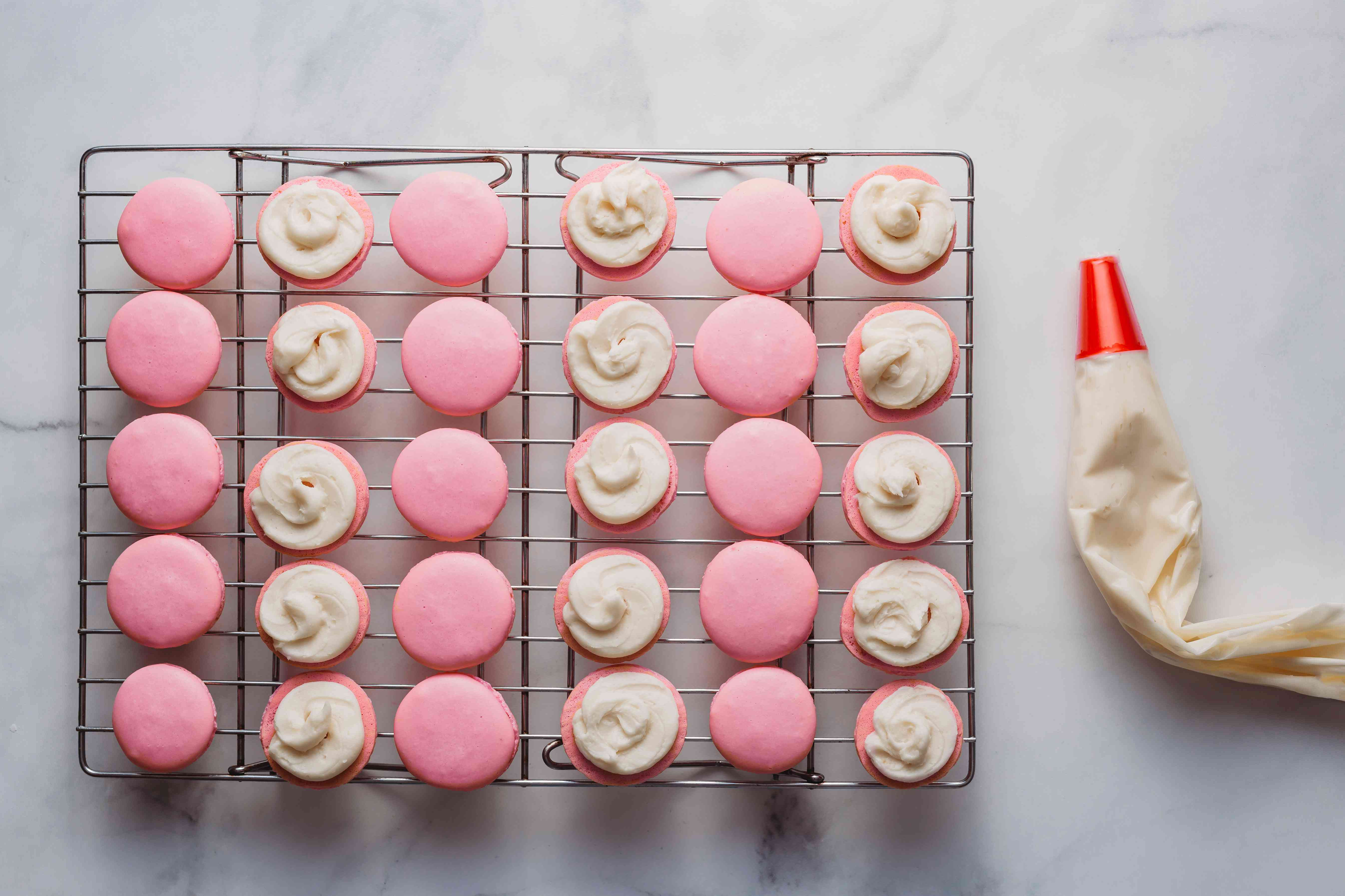 Flip half of the macaron shells upside down and pipe a circle of buttercream onto each shell
