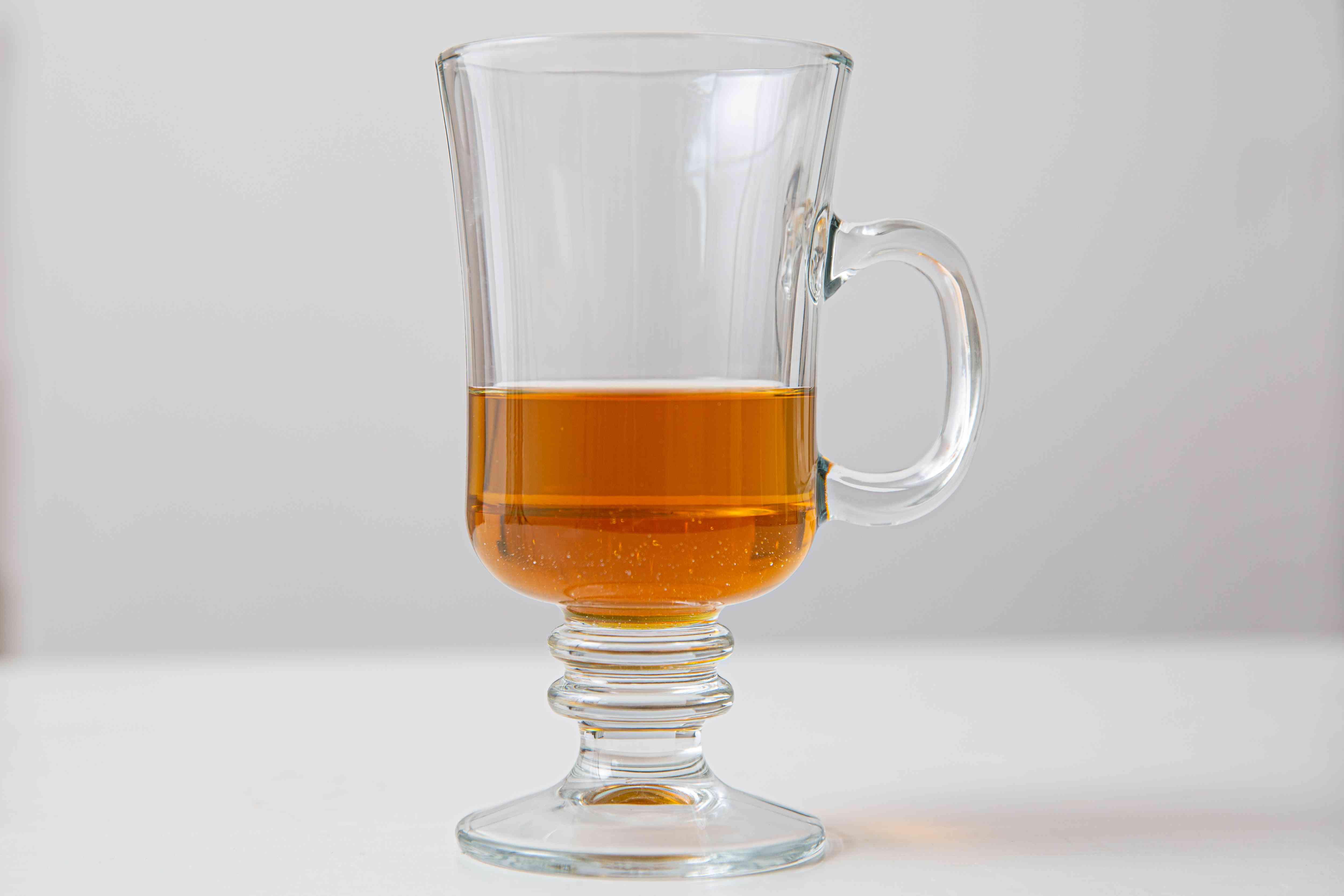 Honey and whiskey in an Irish coffee glass