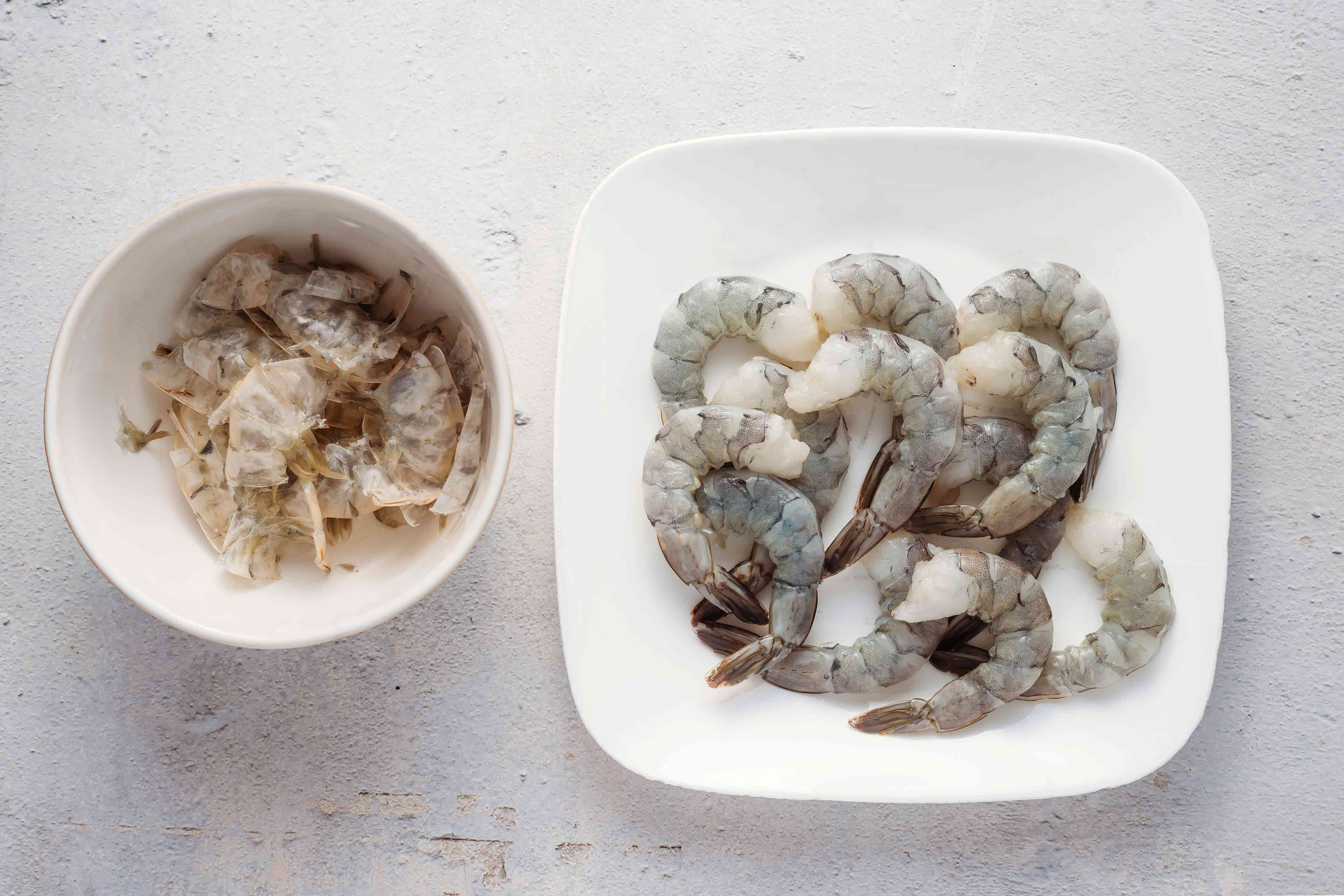 shrimp with shells removed in a bowl, shrimp shells in a bowl