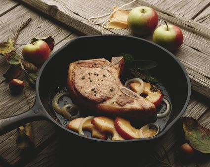 A Pork Chop With Apples and Onions in a Skillet