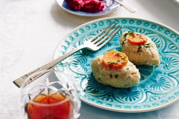 Gefilte fish on a serving dish with a glass of wine and and horseradish in the background