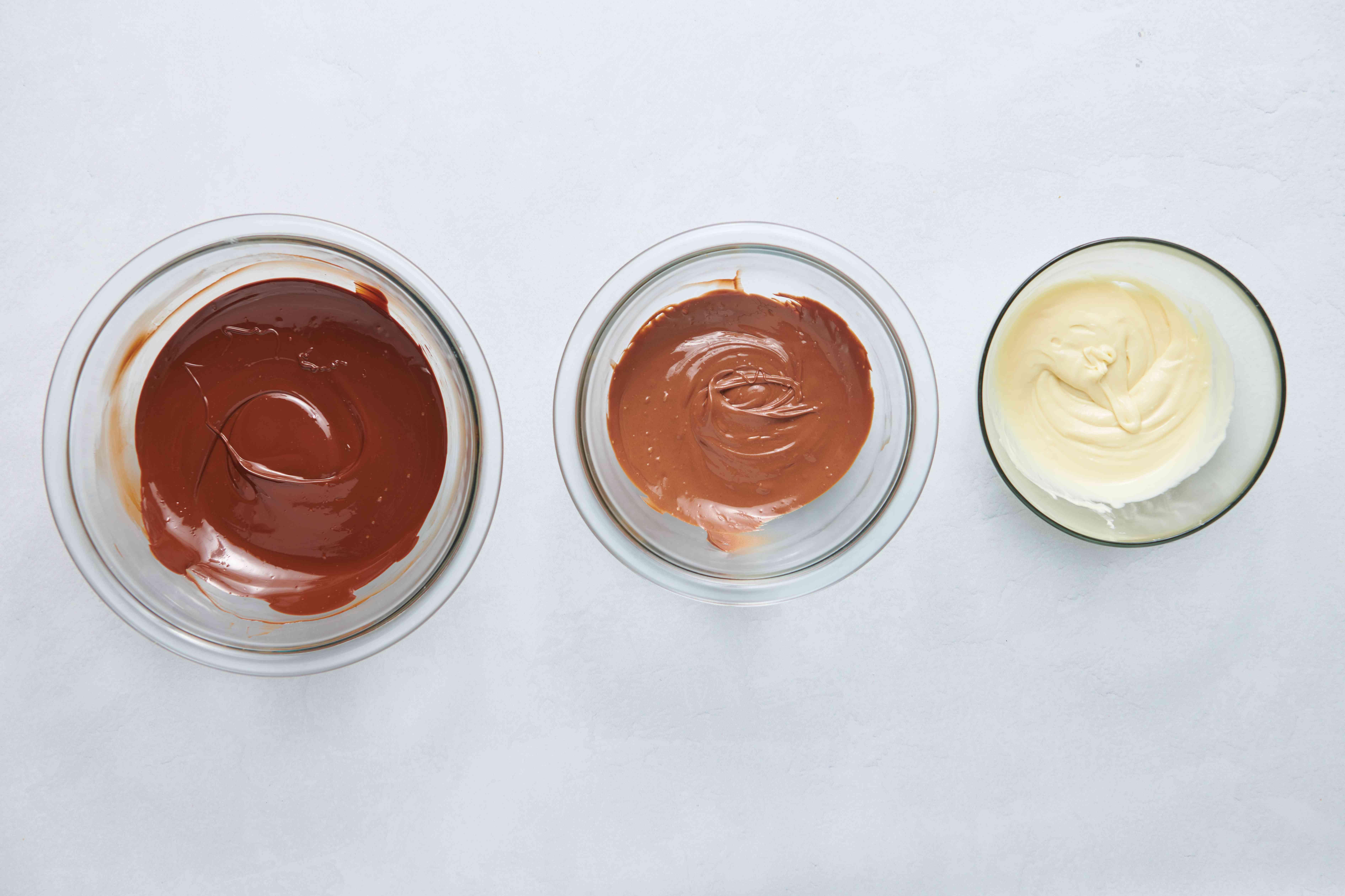 dark, milk and white chocolate in bowls