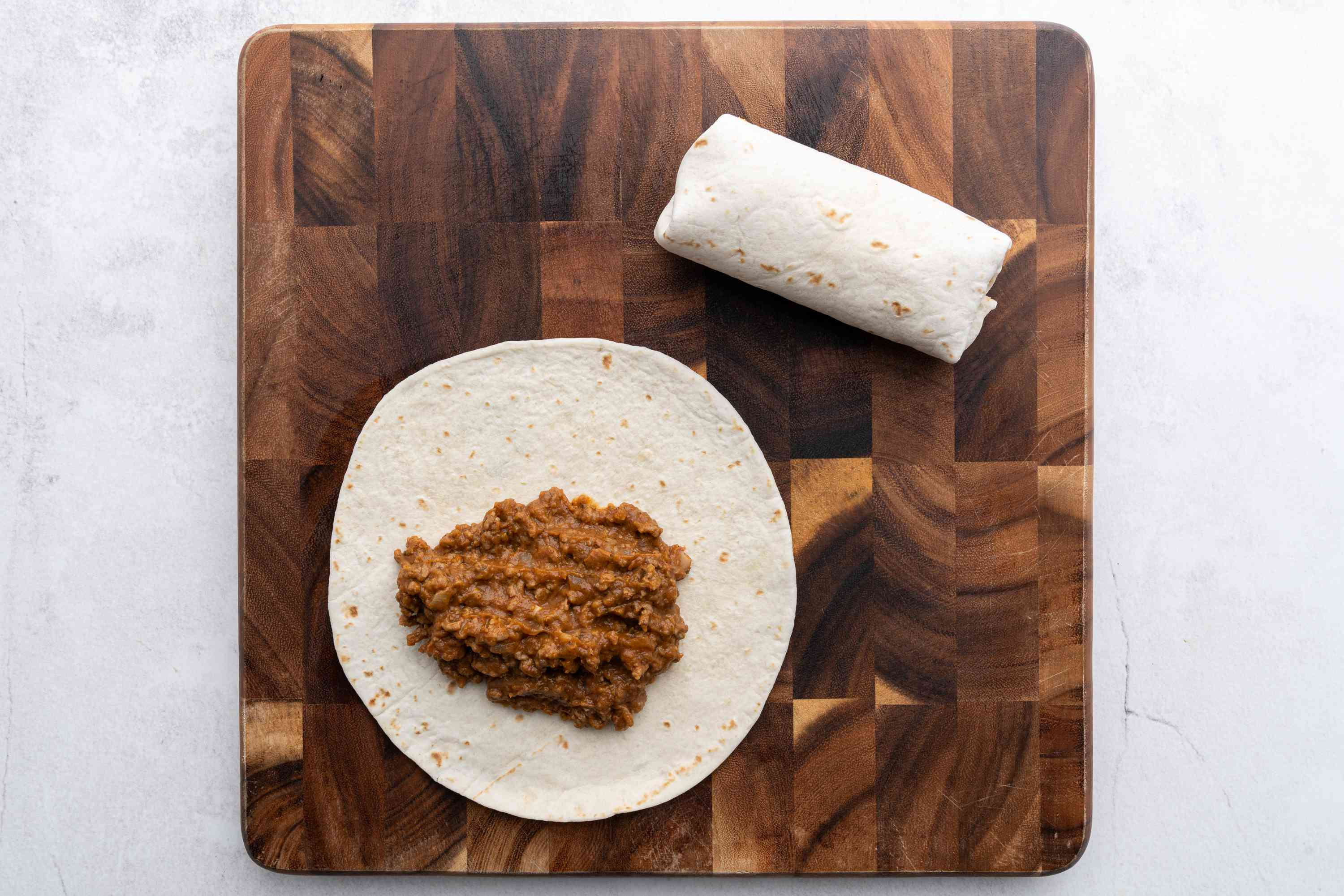 ground beef mixture on top of a tortilla, beef burrito