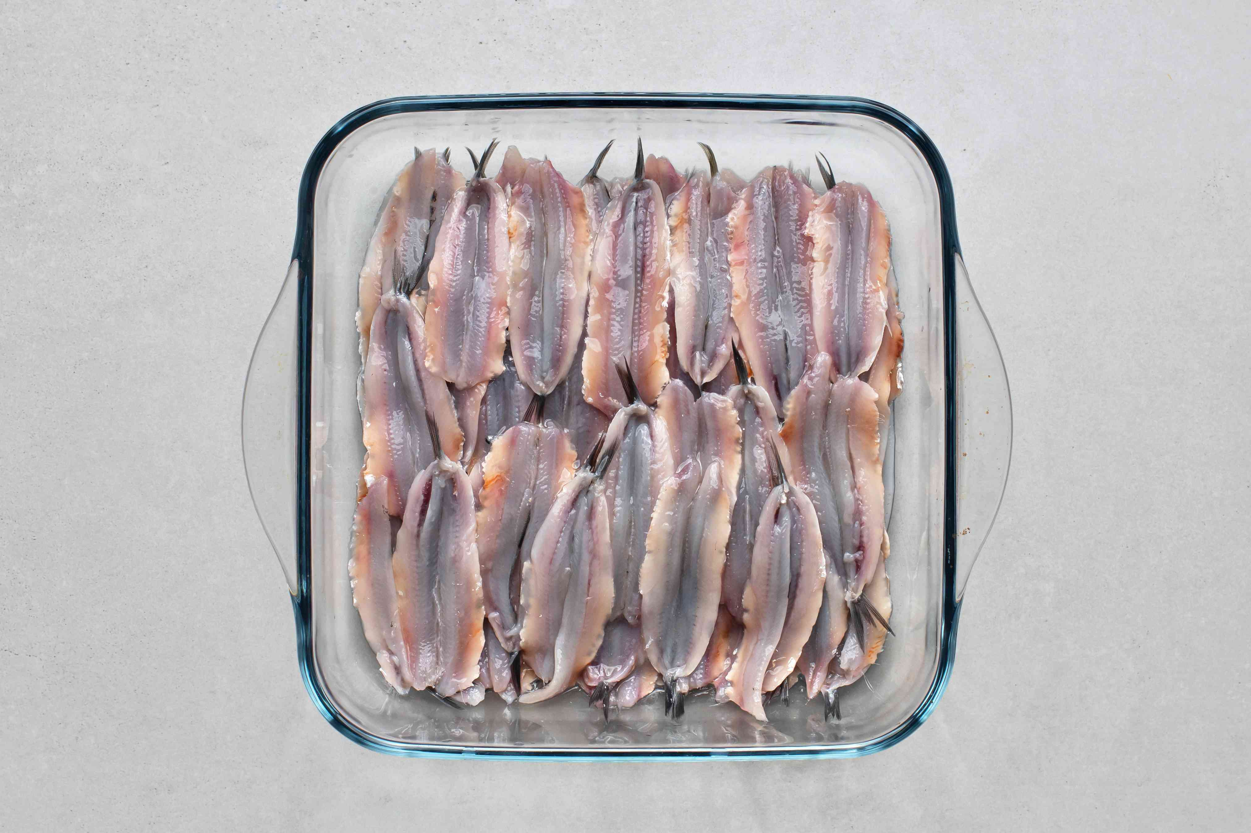 anchovies in a glass baking dish