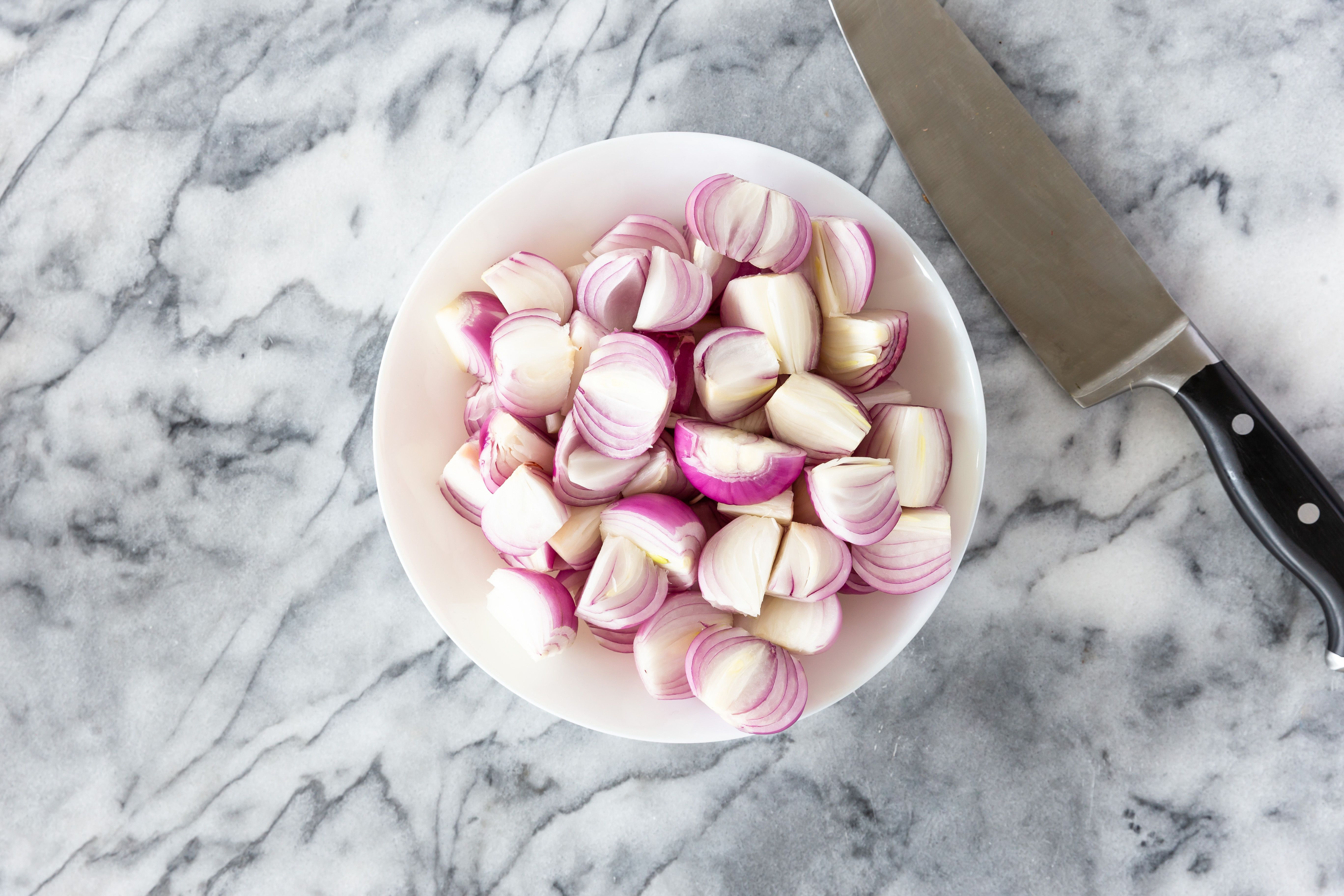 Peeled and halved onions in bowl