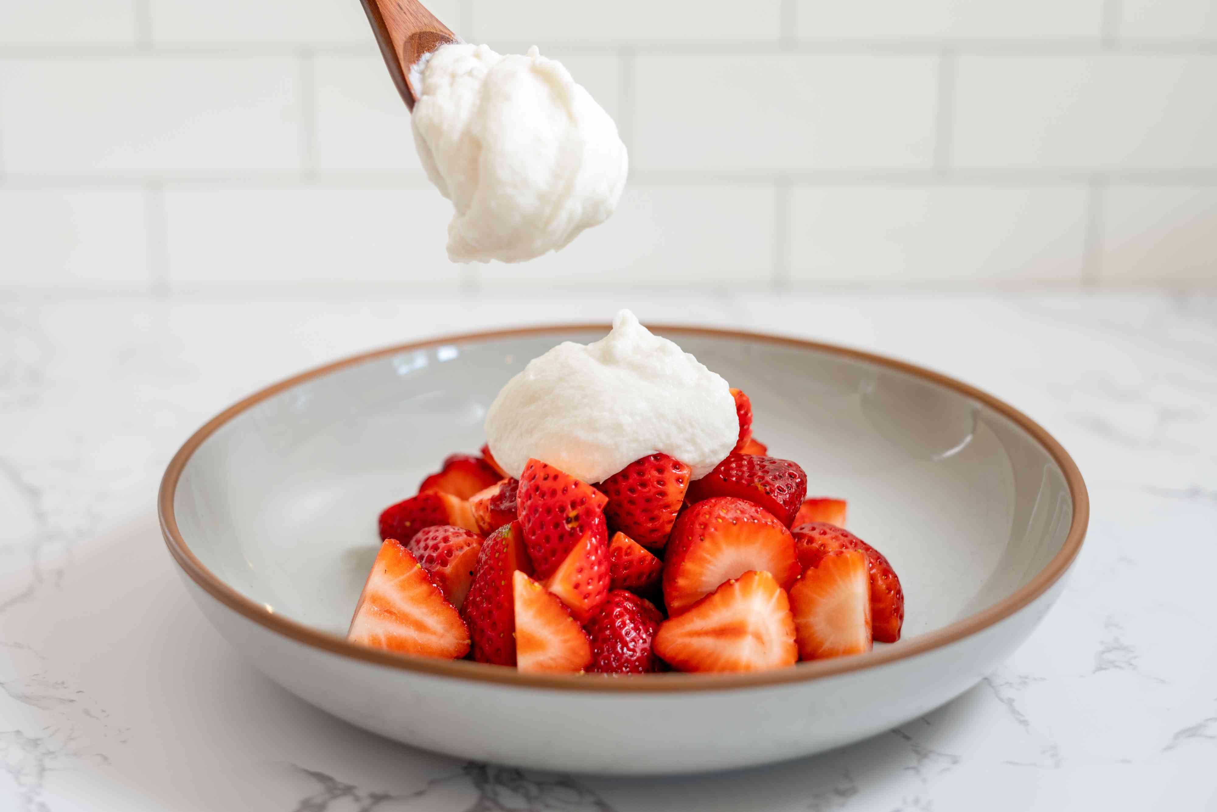 Vegan Whipped Cream on top of strawberries