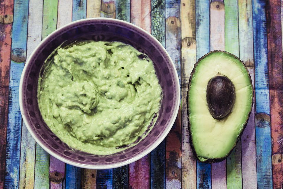 Bowl of guacamole and sliced avocado