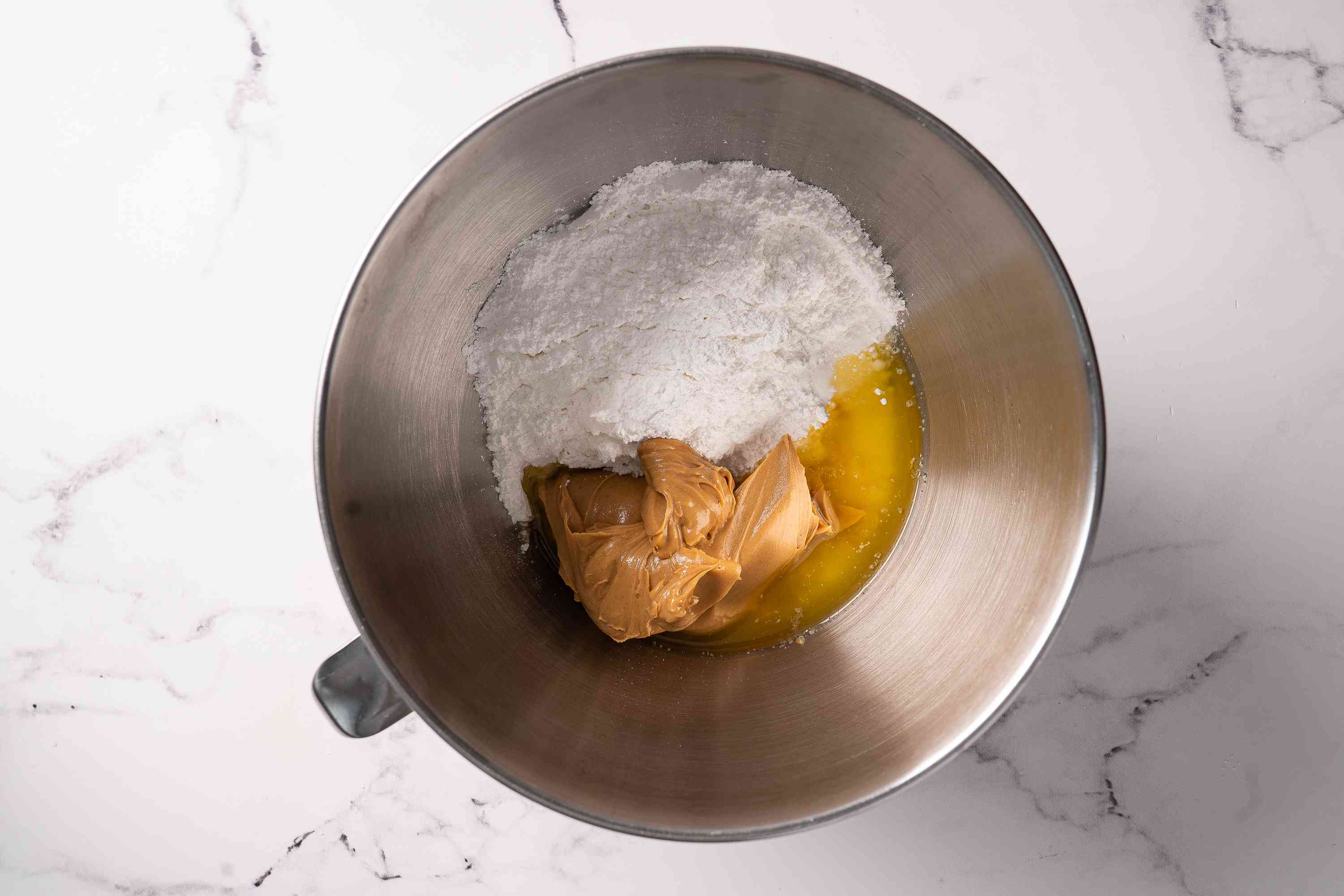 Peanut butter, butter, and powdered sugar in a mixing bowl