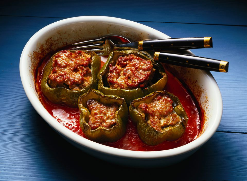 A bowl with four stuffed peppers