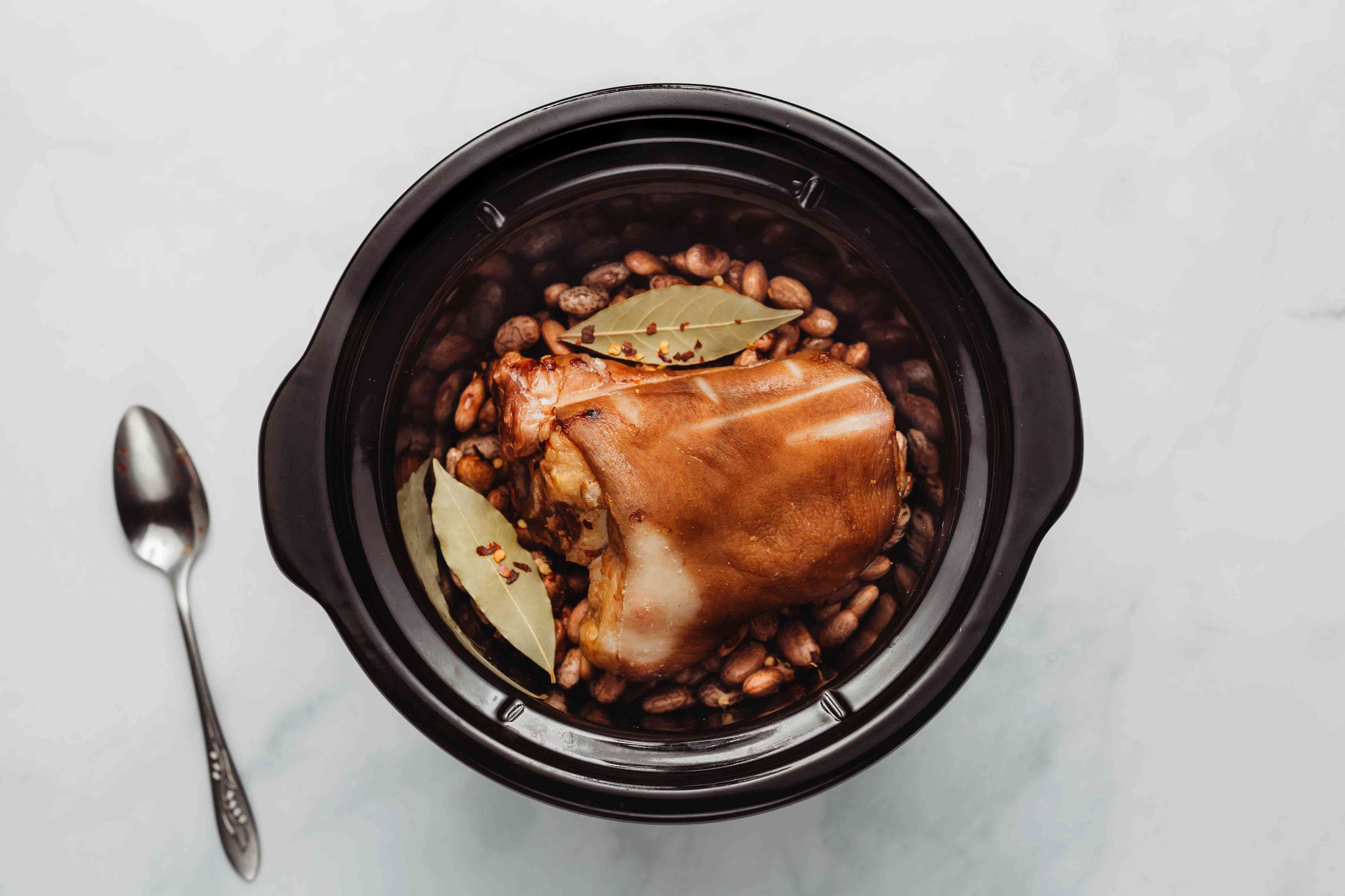 Beans and ham hocks in the crock pot with the bay leaves and crushed red pepper flakes