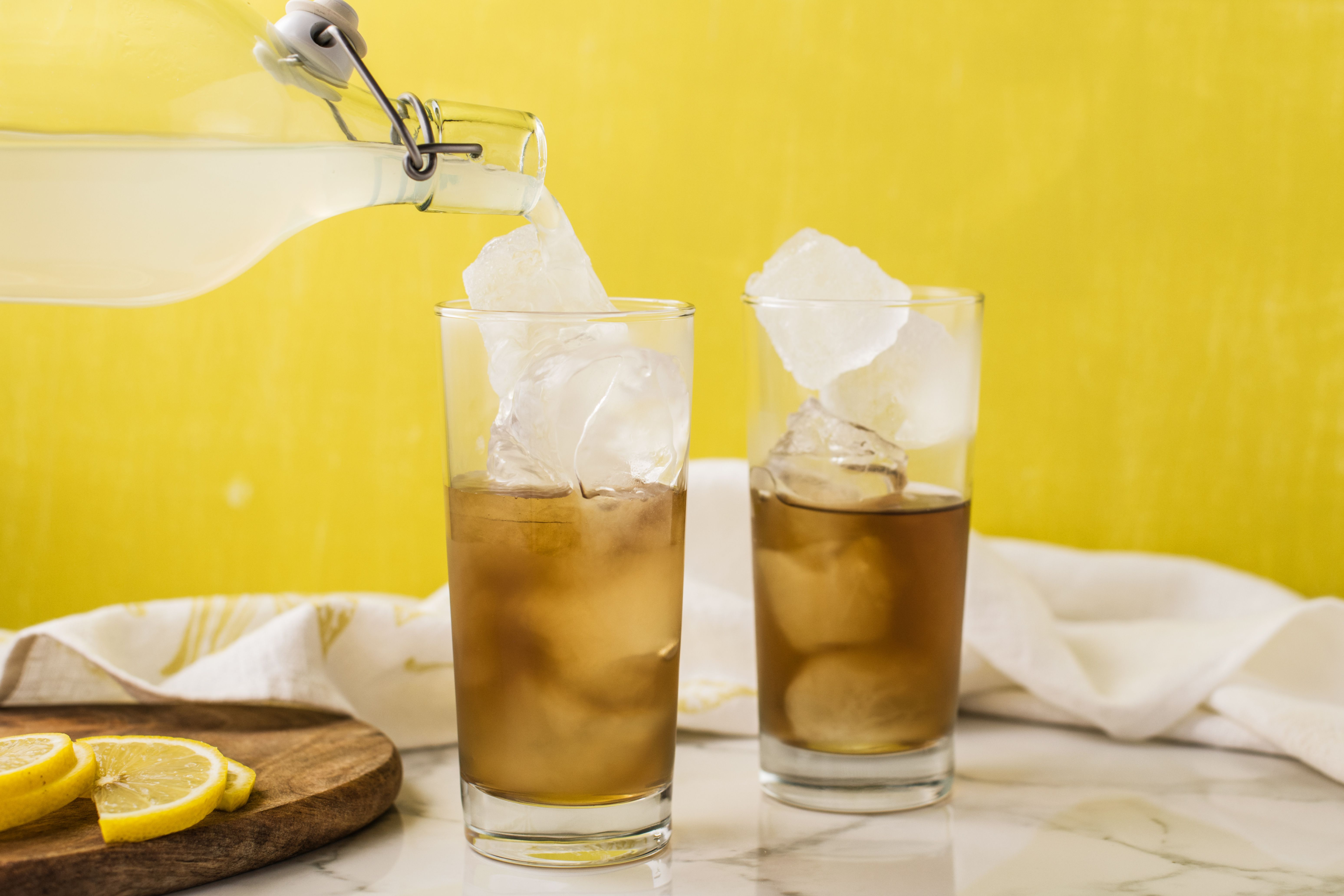 Lemonade being poured into a glass of iced tea