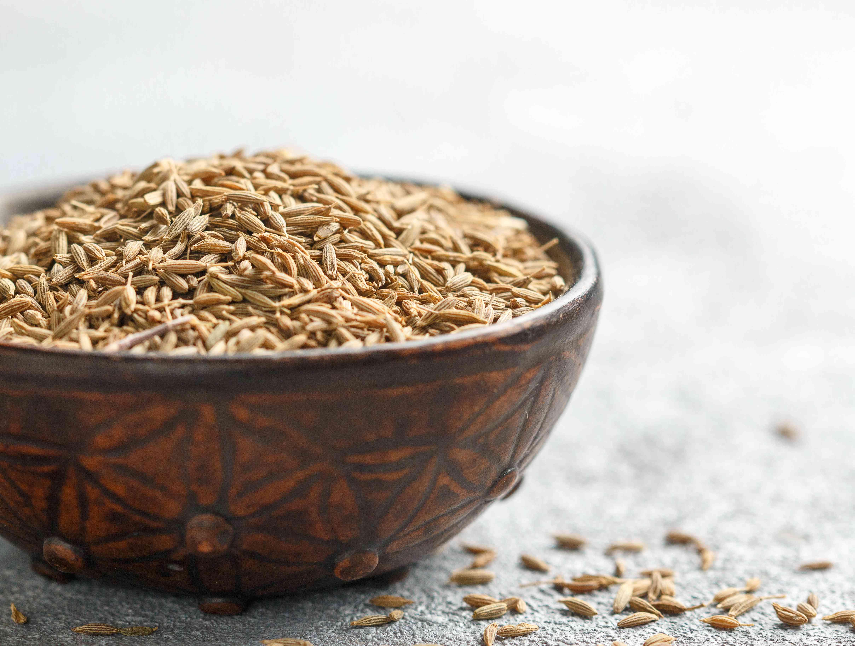 Cumin seeds (Zira) in a ceramic bowl close-up. Seasoning. Condiment
