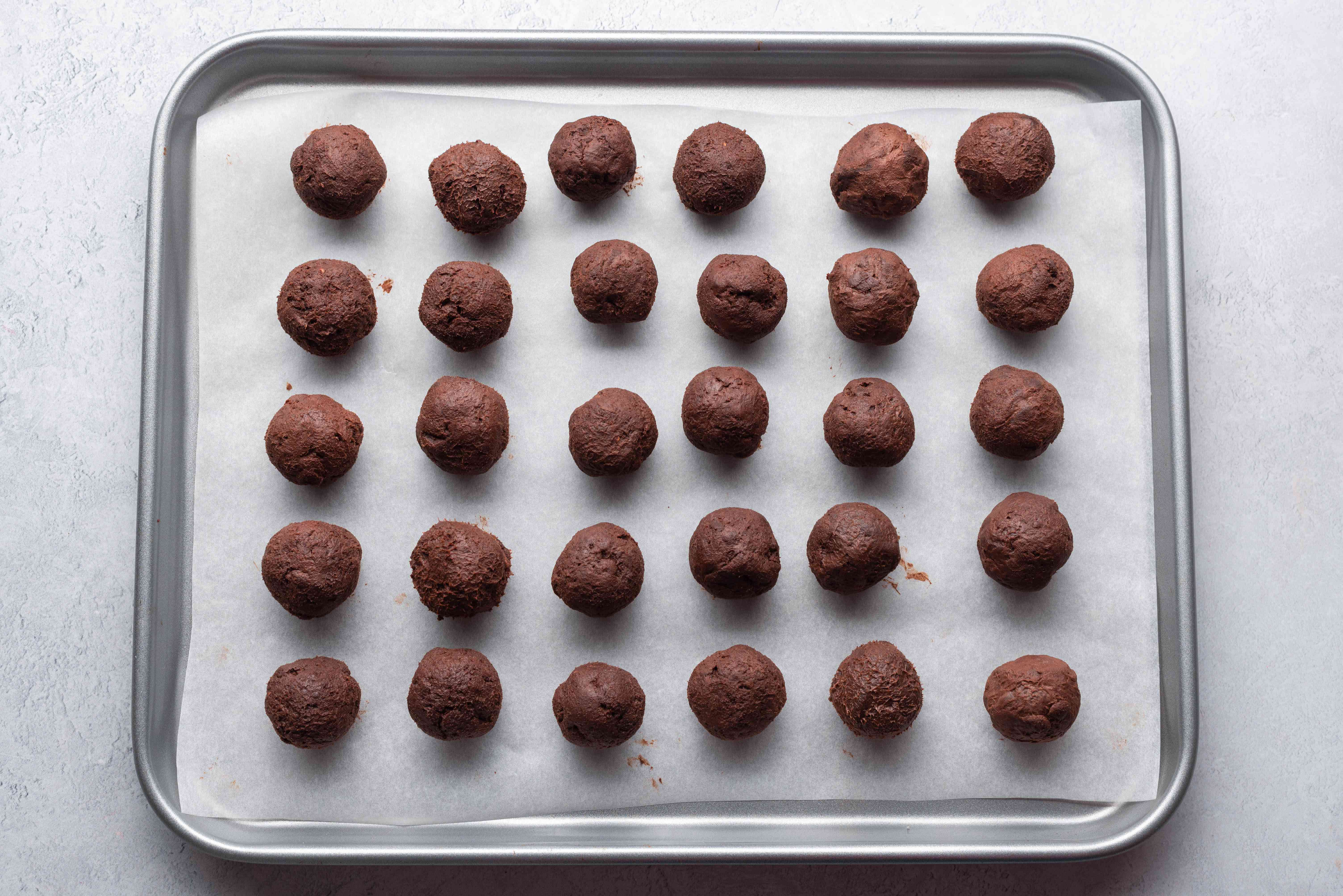 chocolate balls on a parchment paper lined baking sheet