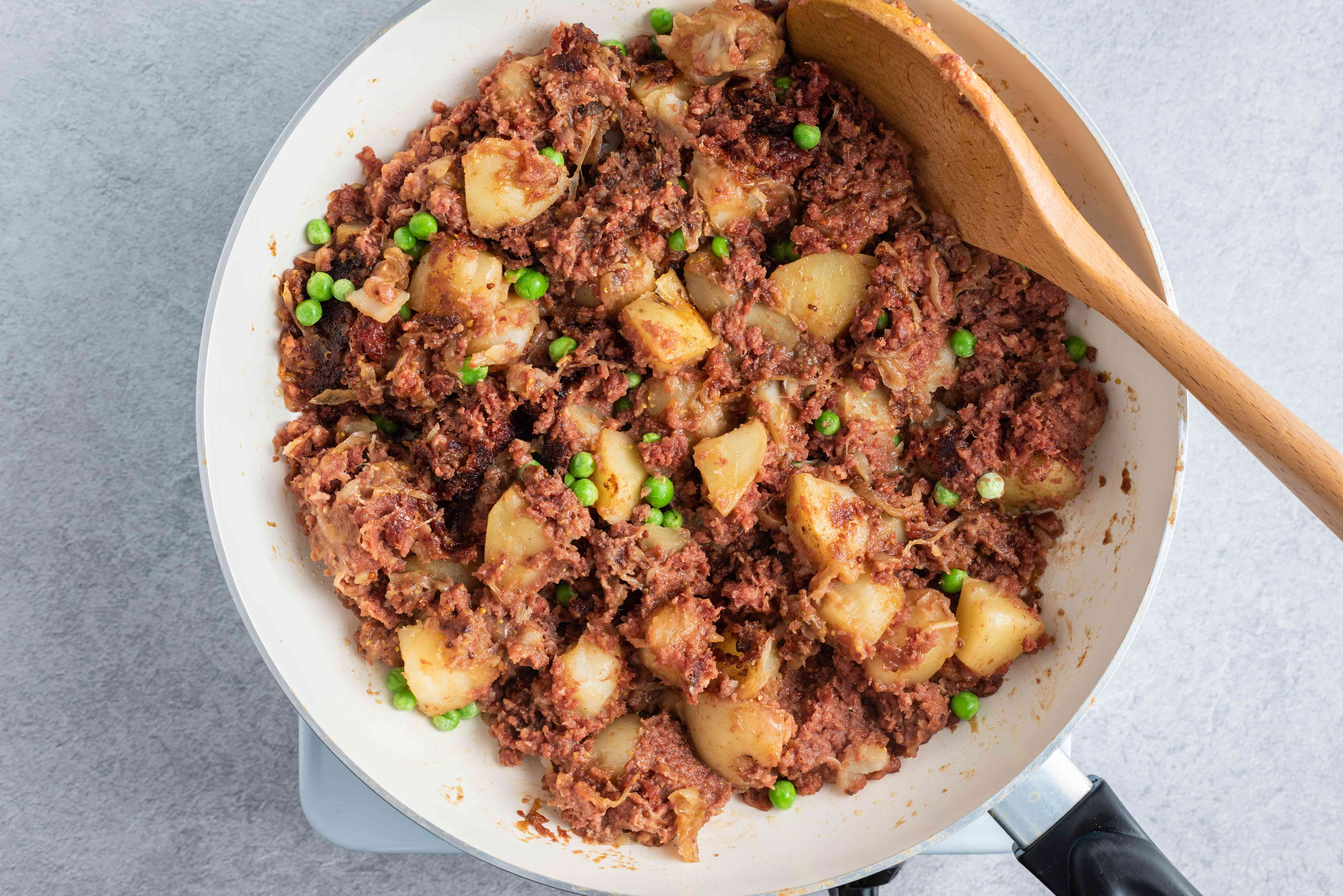 mixing corned beef with potatoes onions and peas in a large frying pan